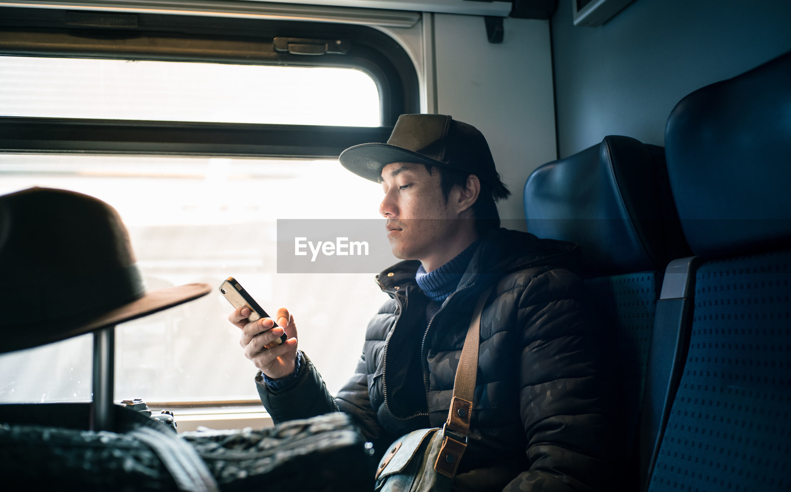 Man using mobile phone while sitting in train