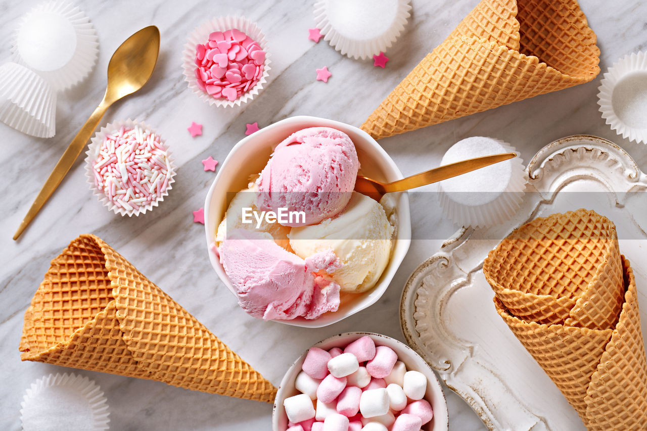 High Angle View Of Ice Cream Served In Bowl By Candies And Cones On Floor