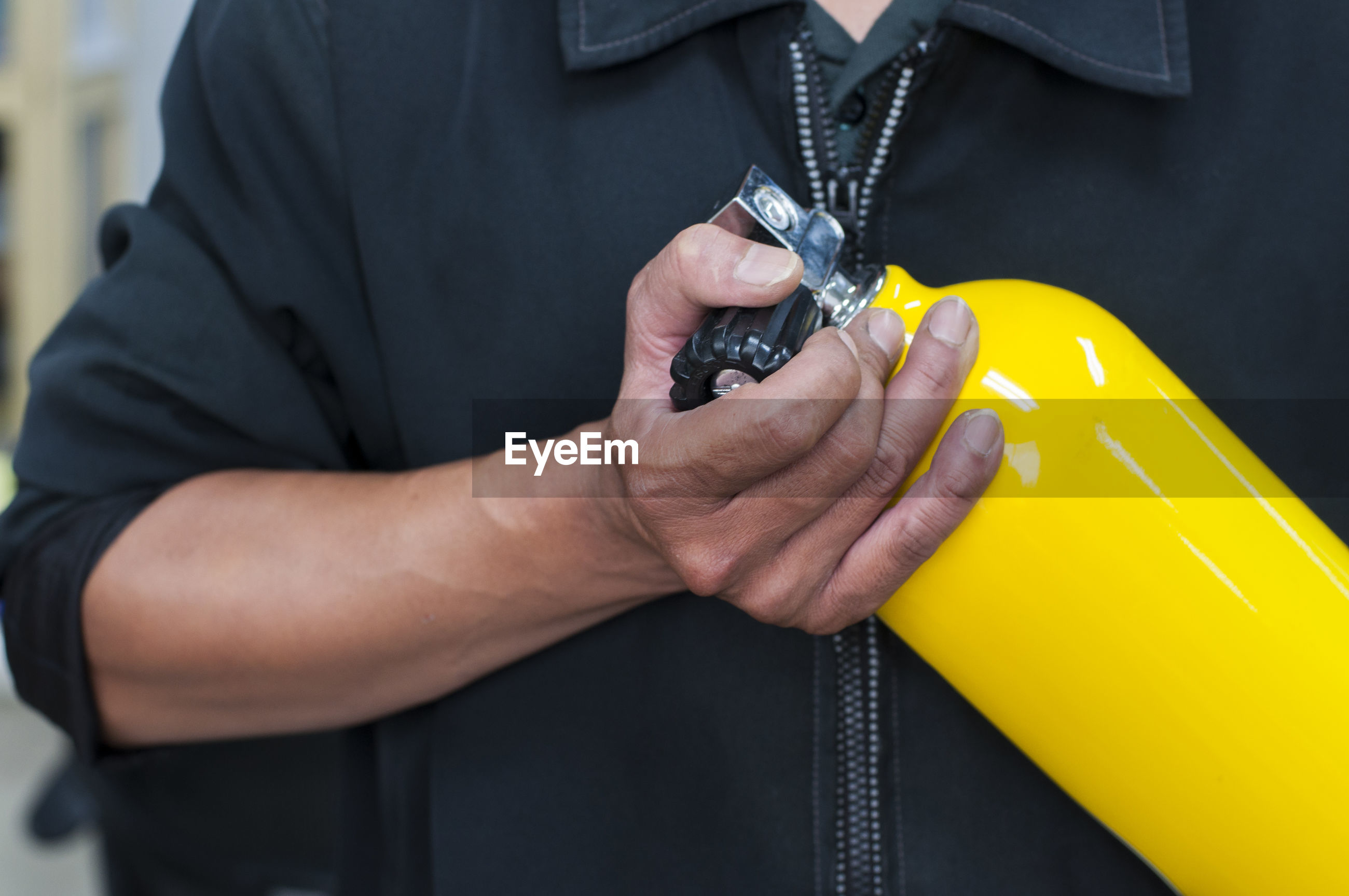 Close-up midsection of man holding diving equipment