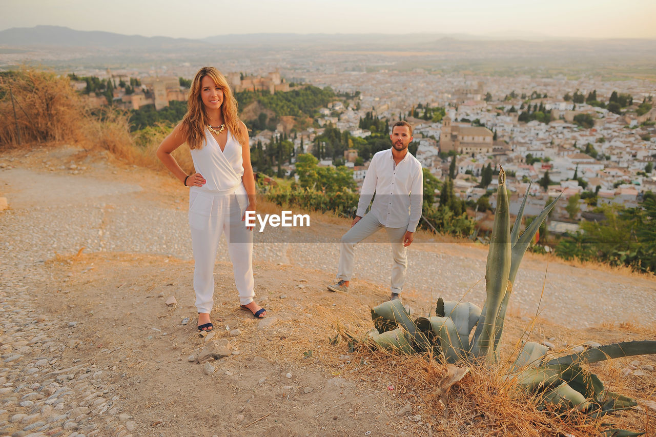 Portrait Of Couple Standing On Cobbled Road During Sunset