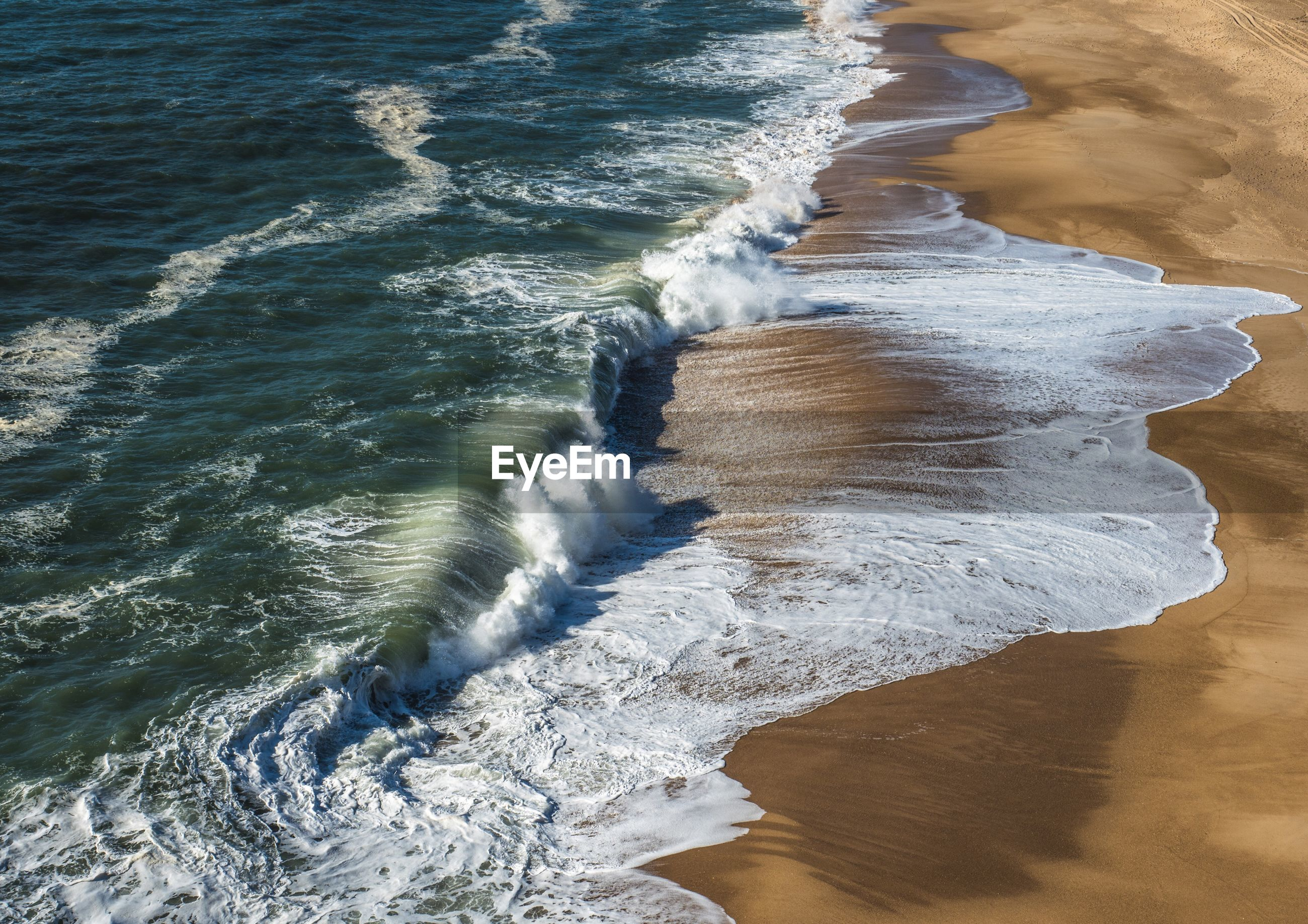 HIGH ANGLE VIEW OF WAVES ON SHORE