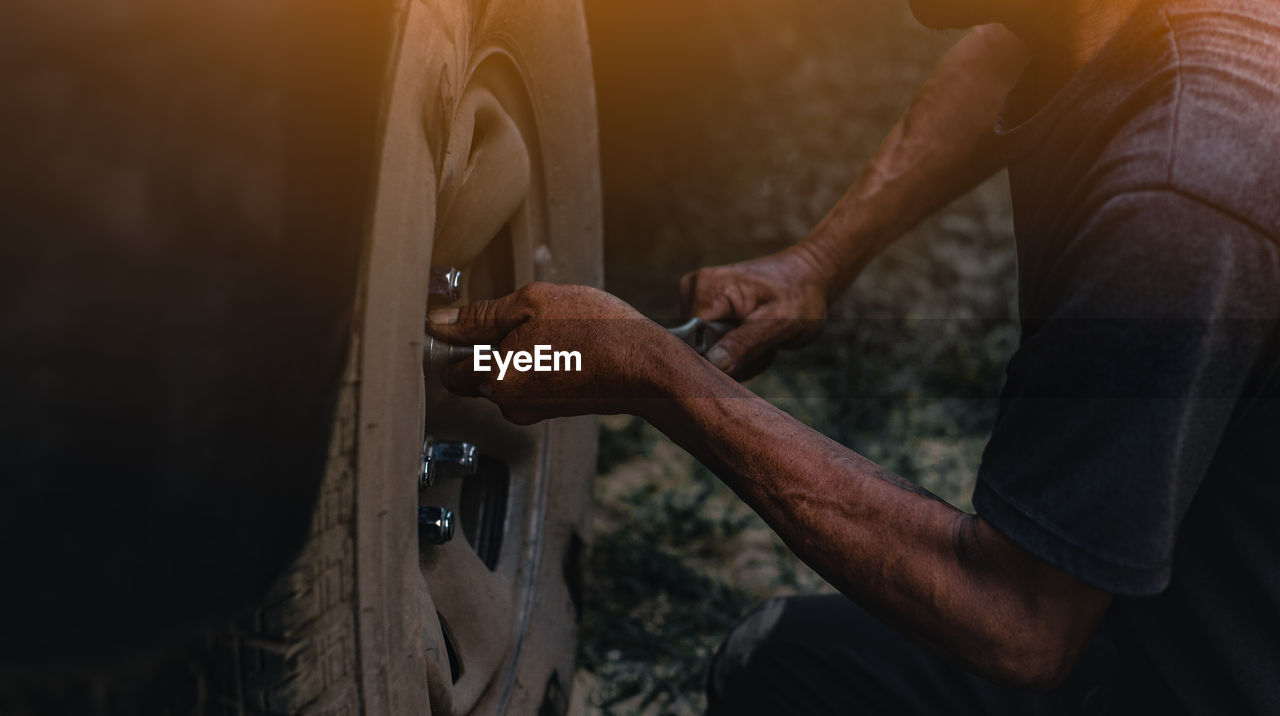 one person, real people, men, occupation, holding, hand, human hand, working, skill, wheel, human body part, day, focus on foreground, close-up, lifestyles, indoors, repairing, tool, tire, human limb, mechanic
