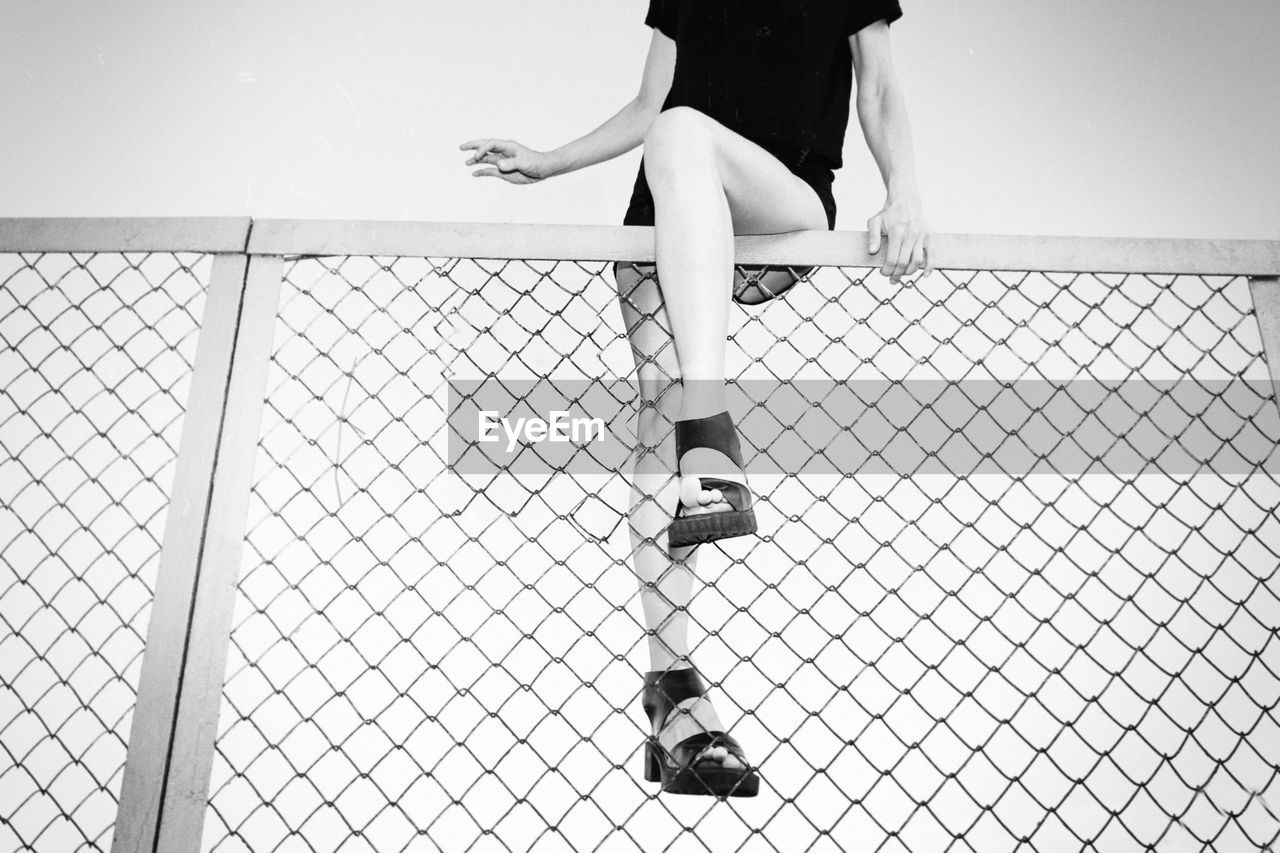 Low Angle View Of Young Woman Sitting On Chainlink Fence