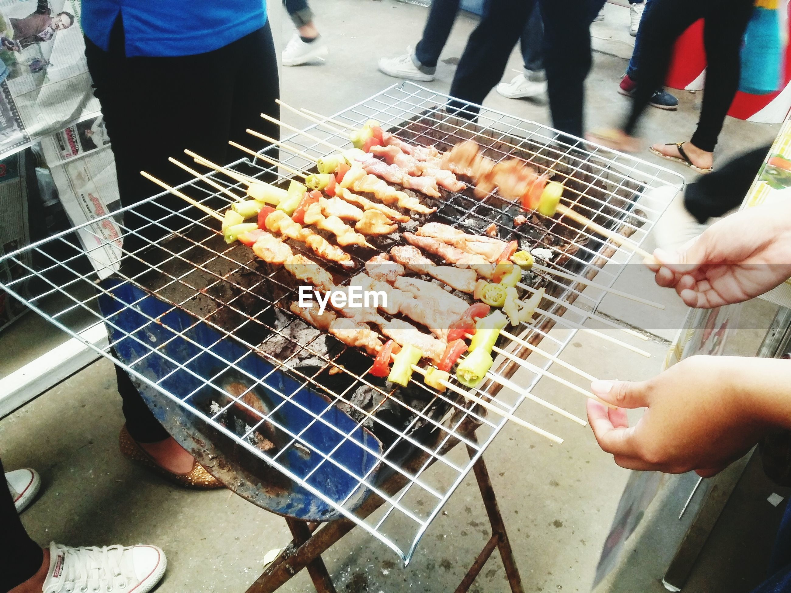 real people, food and drink, freshness, food, human hand, skewer, high angle view, grilled, holding, medium group of people, barbecue, lifestyles, barbecue grill, meat, day, ready-to-eat, street food, outdoors, men, healthy eating, human body part, people