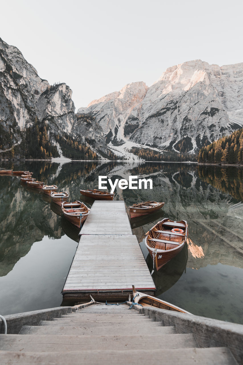 mountain, water, scenics - nature, nature, beauty in nature, day, no people, mountain range, nautical vessel, lake, transportation, sky, tranquility, tranquil scene, non-urban scene, winter, wood - material, cold temperature, outdoors, rowboat, snowcapped mountain