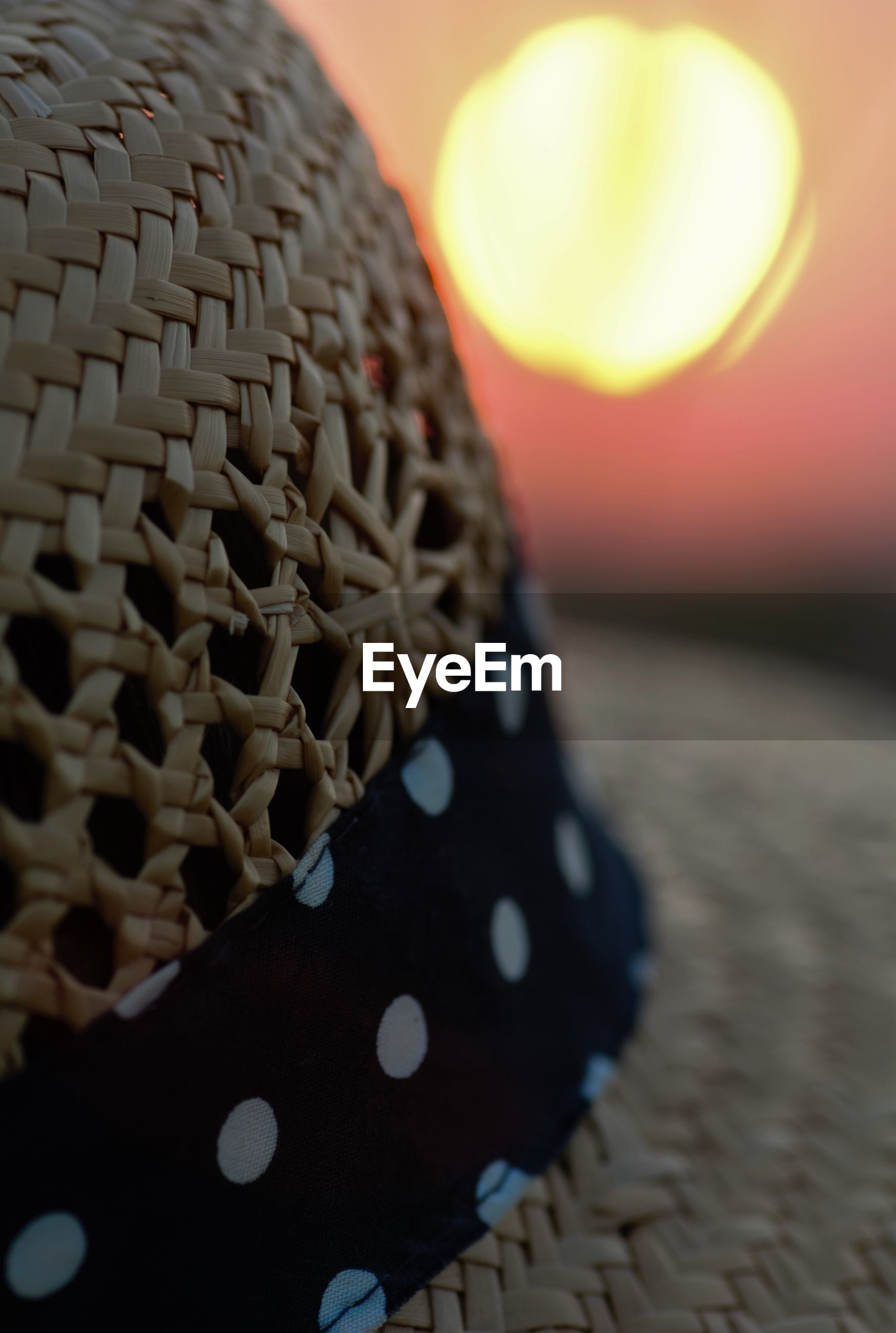Close-up of straw hat against sun during sunset