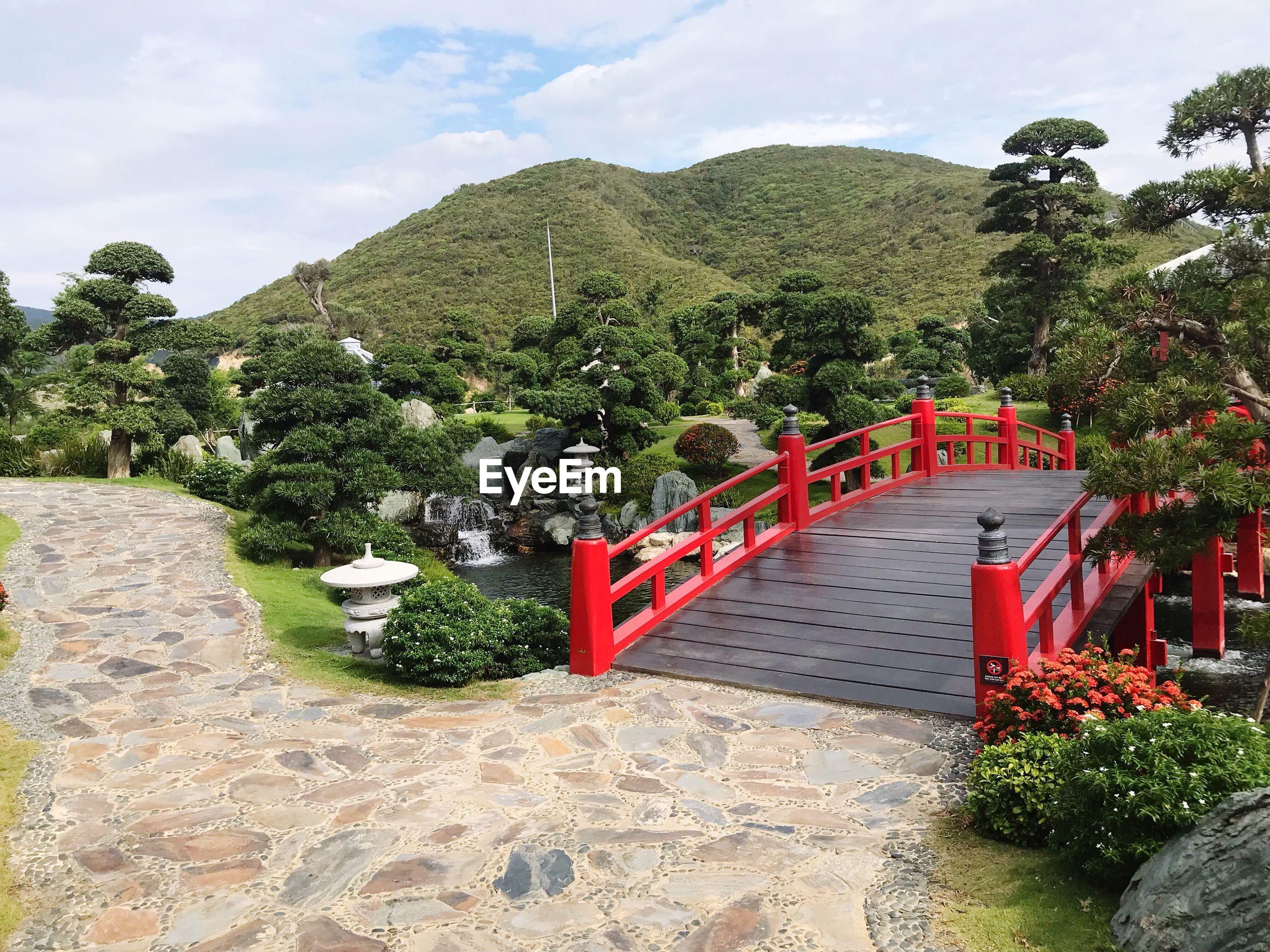 Footbridge in garden against mountain