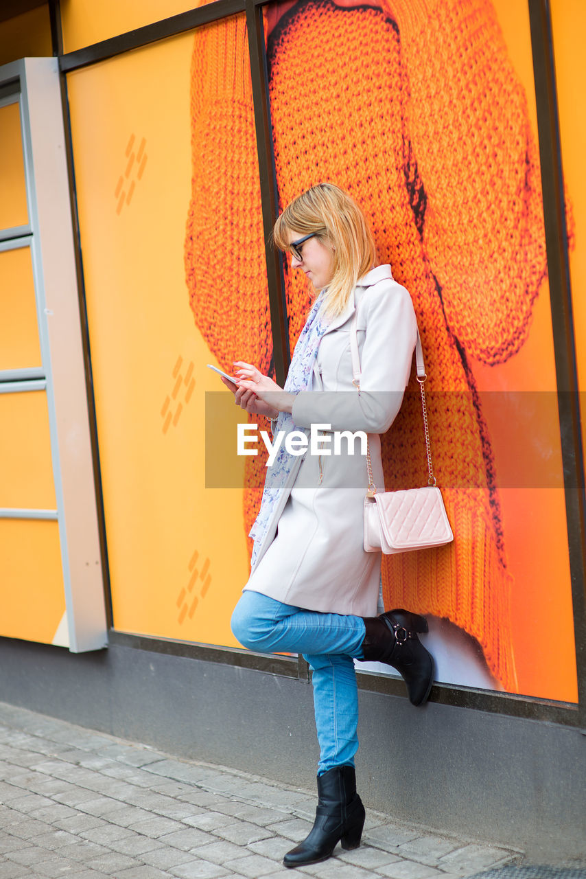 Young Woman Using Phone Against Orange Wall
