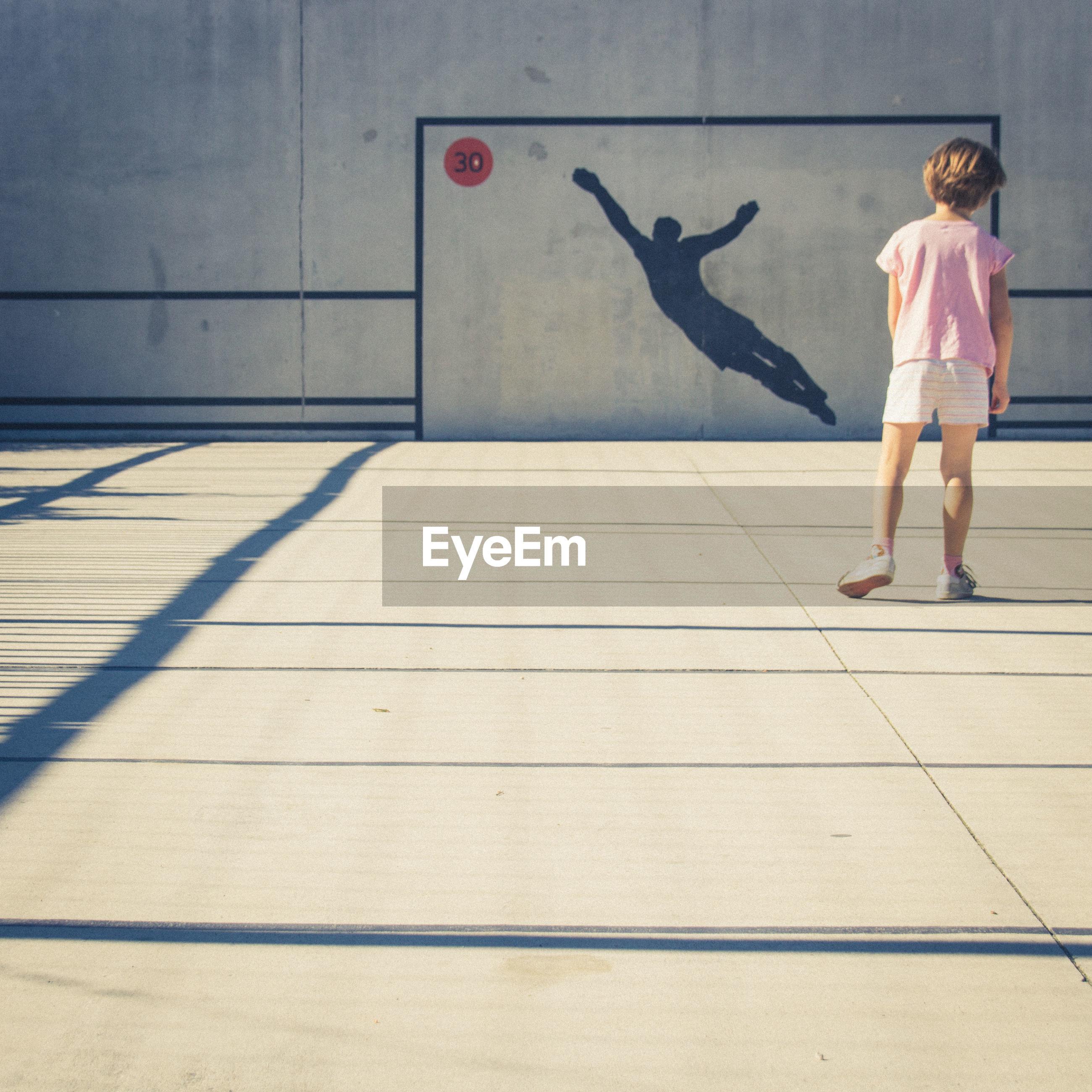 Full length rear view of girl standing in basketball court