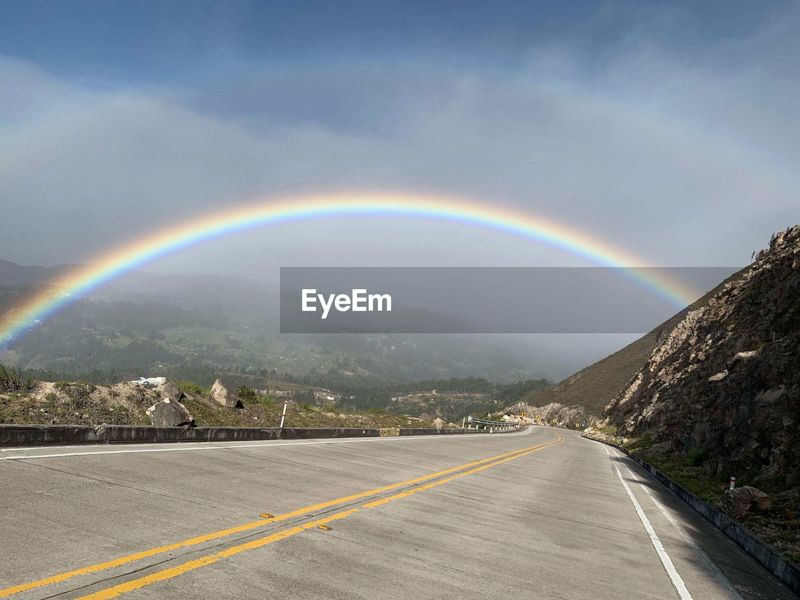 Double rainbow over road against sky