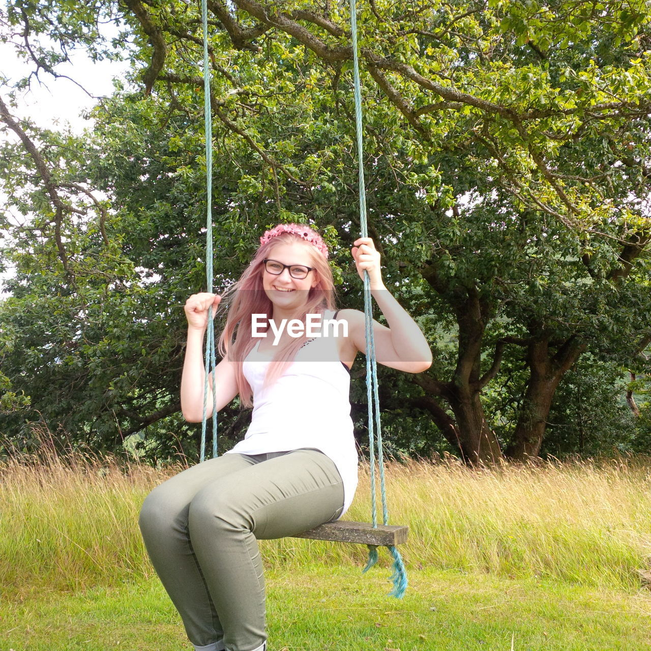 tree, smiling, looking at camera, real people, leisure activity, one person, happiness, casual clothing, rope swing, portrait, young women, day, full length, front view, young adult, lifestyles, growth, swing, holding, outdoors, grass, nature, cheerful, beautiful woman