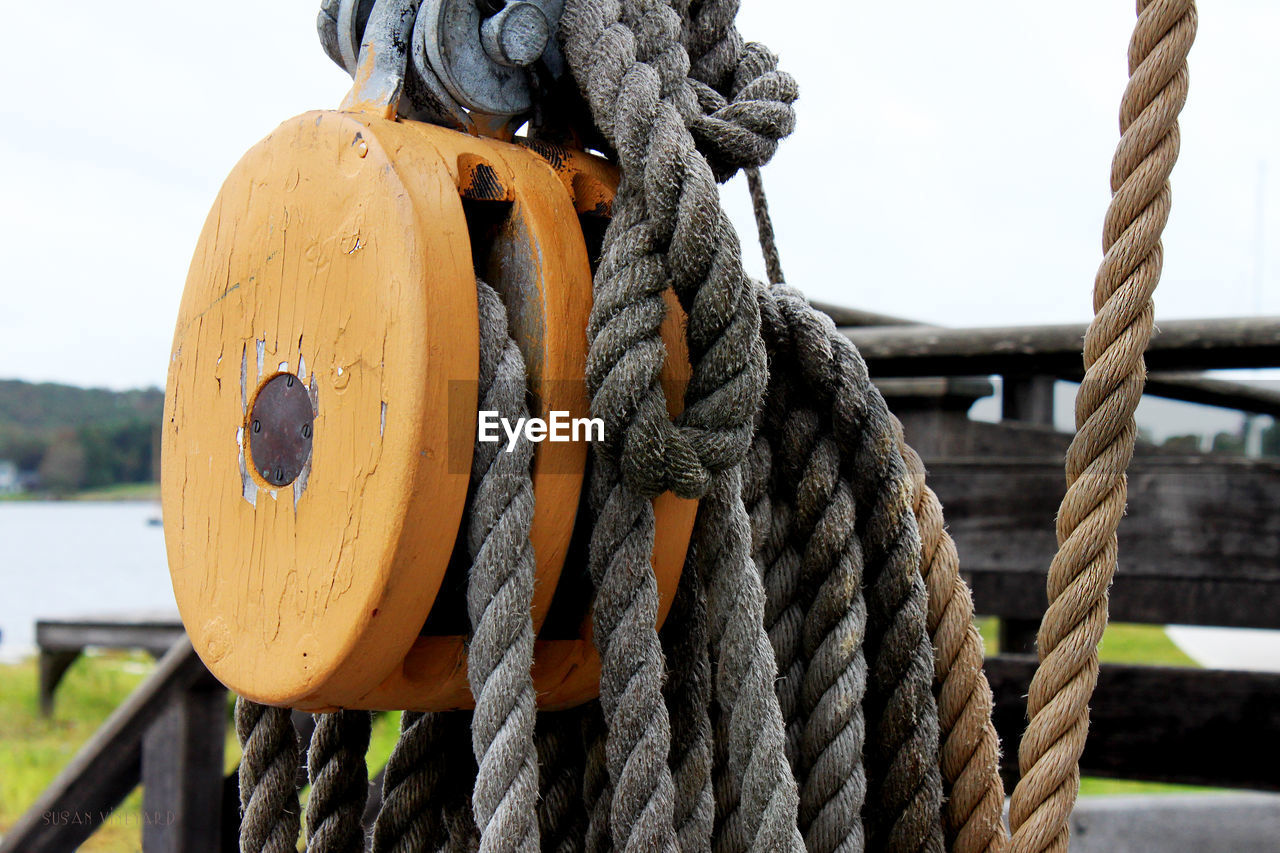 rope, strength, focus on foreground, tied up, close-up, nautical vessel, transportation, no people, wood - material, day, mode of transportation, connection, metal, post, sky, water, nature, outdoors, pulley, durability, wooden post
