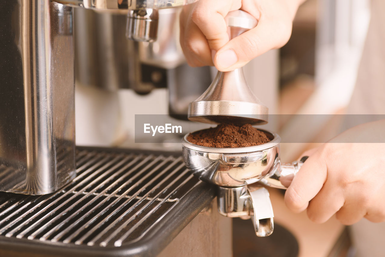 Close-Up Of Hands Holding Coffee Maker