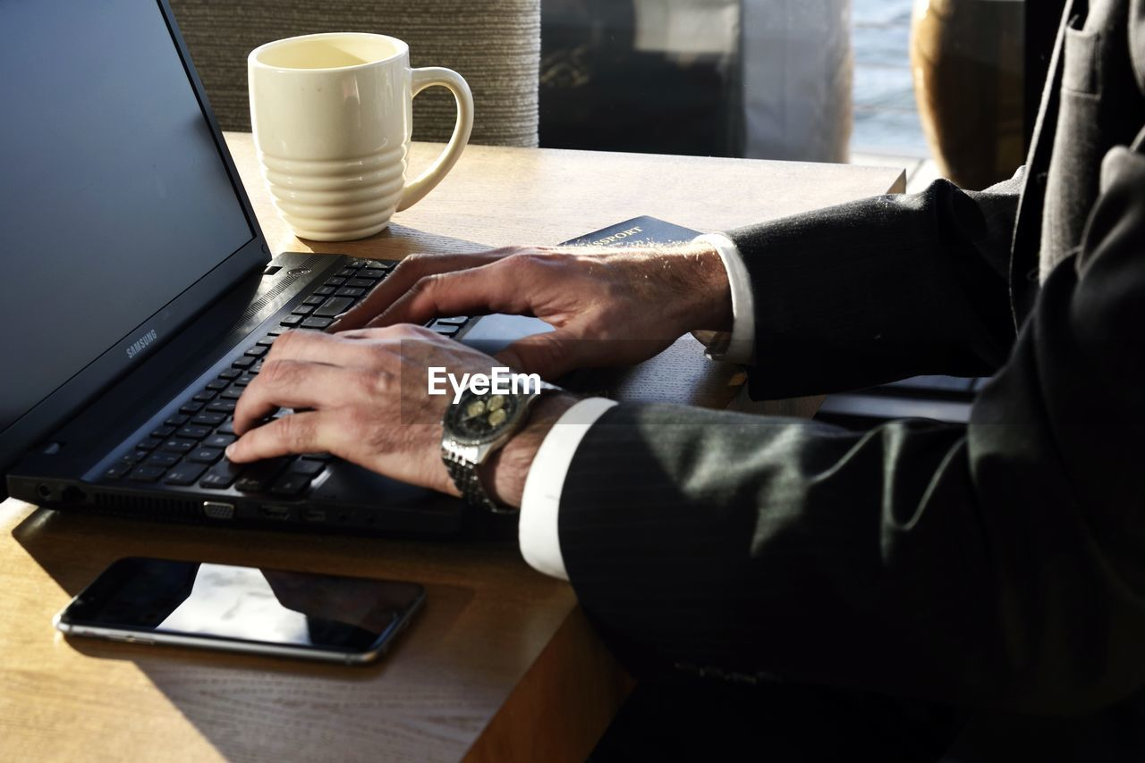 technology, human hand, laptop, wireless technology, men, desk, indoors, connection, real people, sitting, table, communication, midsection, computer, human body part, using laptop, well-dressed, two people, working, businessman, wristwatch, occupation, computer keyboard, day, close-up, people