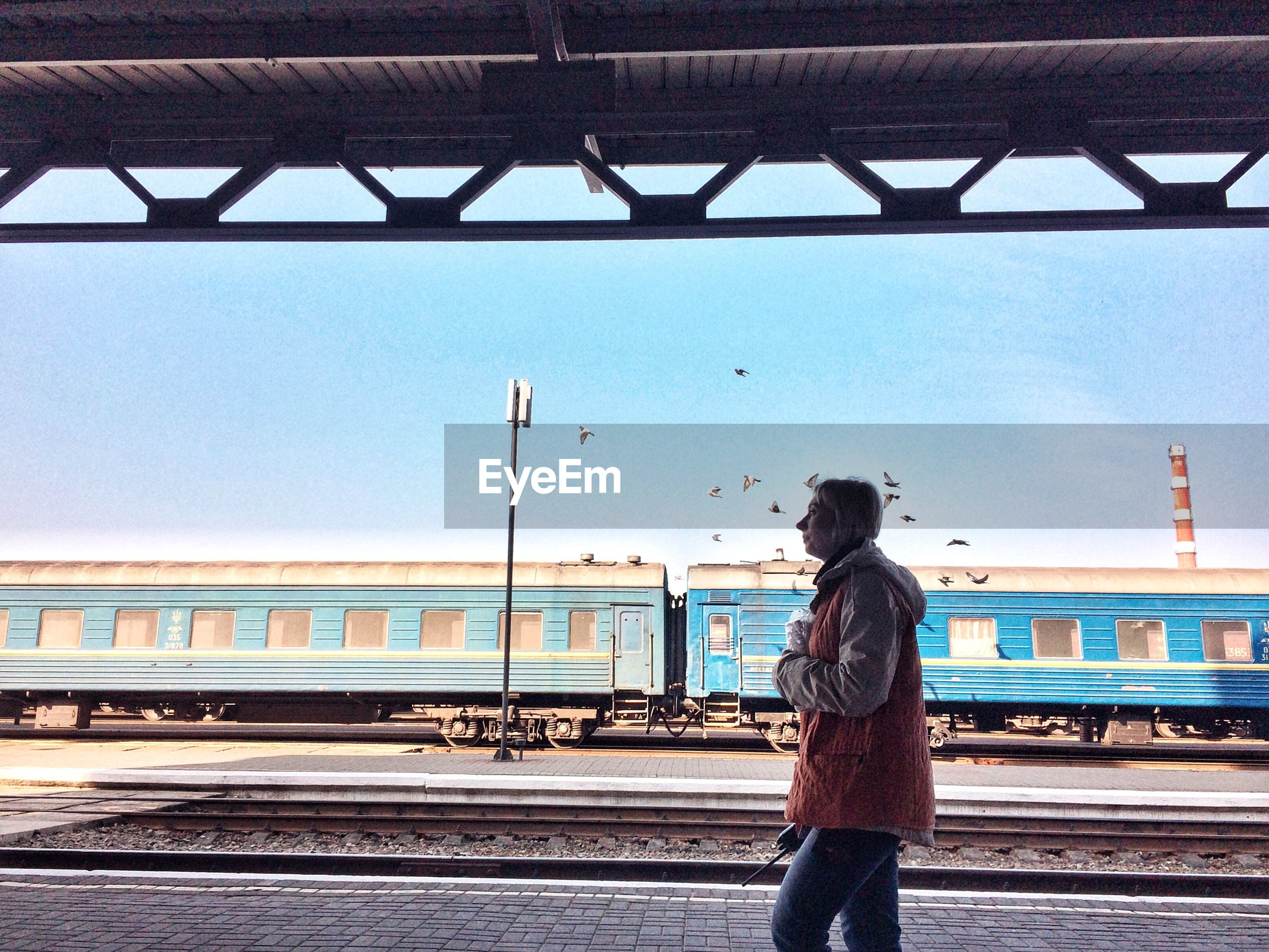 rail transportation, sky, transportation, real people, public transportation, railroad track, track, one person, lifestyles, train, railroad station, railroad station platform, casual clothing, architecture, leisure activity, standing, built structure, train - vehicle, mode of transportation, rear view, outdoors, hairstyle, waiting
