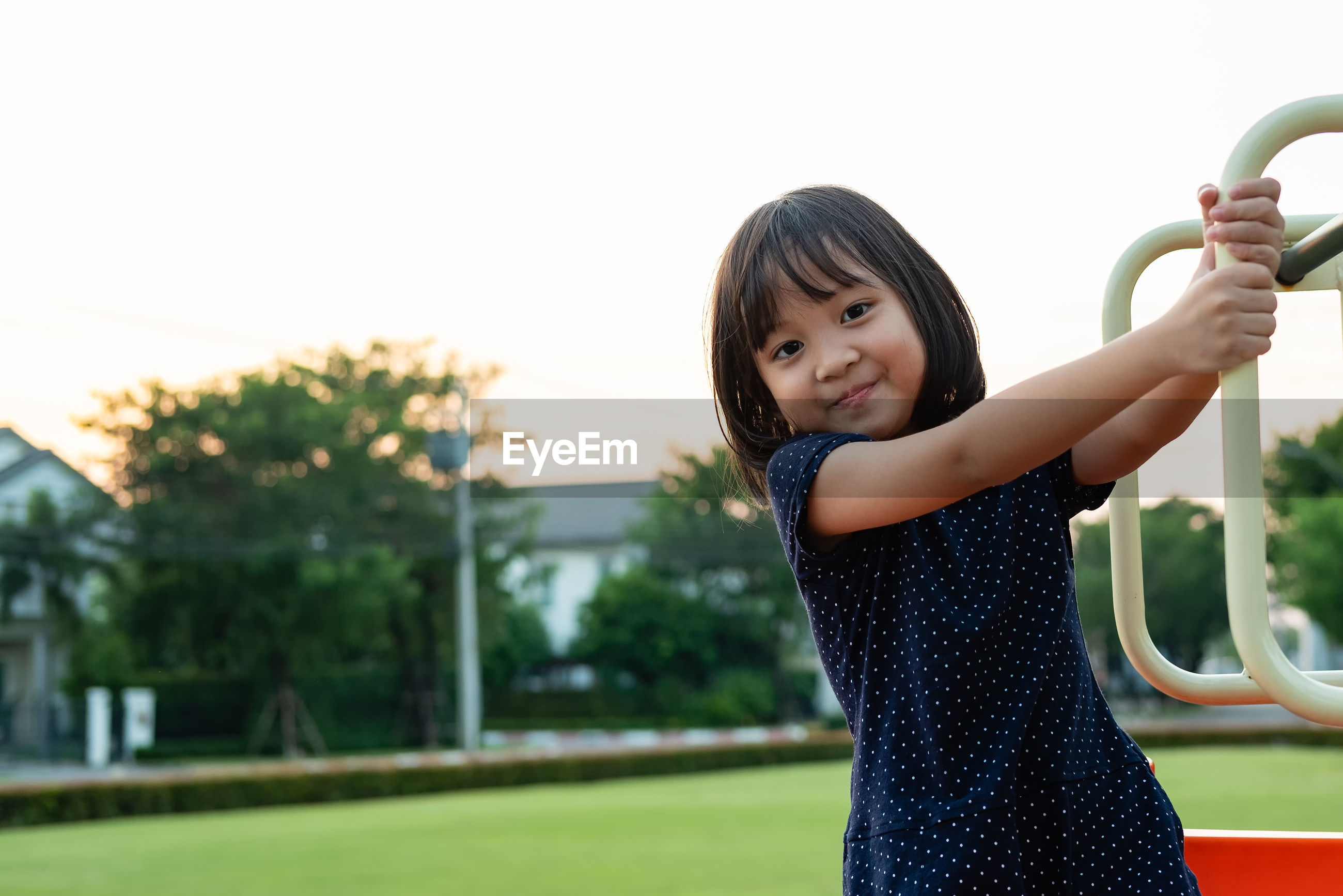 Portrait of smiling girl hanging on outdoor play equipment against clear sky in park