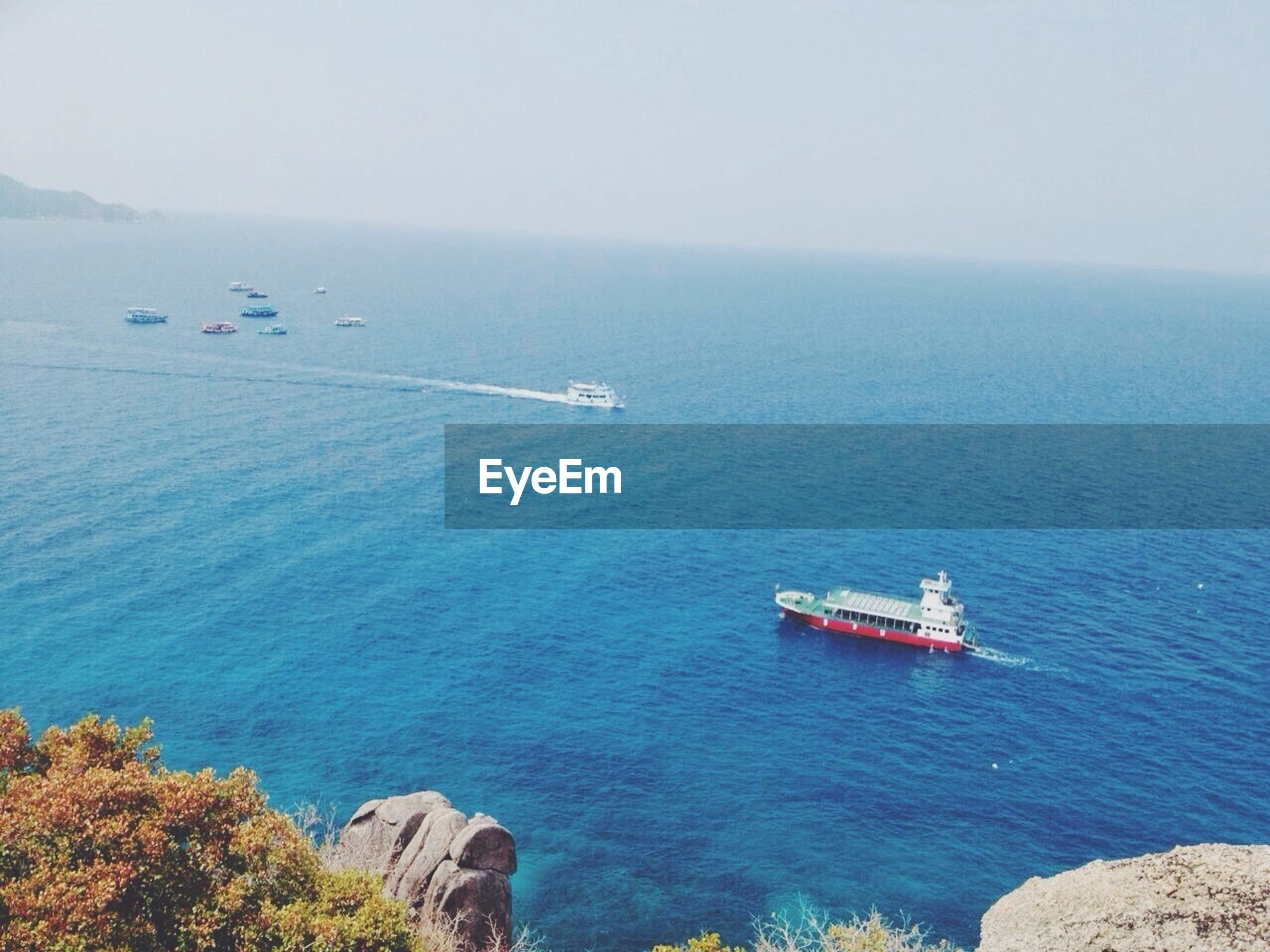 sea, water, transportation, nautical vessel, mode of transport, boat, horizon over water, high angle view, scenics, tranquil scene, beauty in nature, sailing, tranquility, travel, nature, blue, cliff, day, rock - object, idyllic