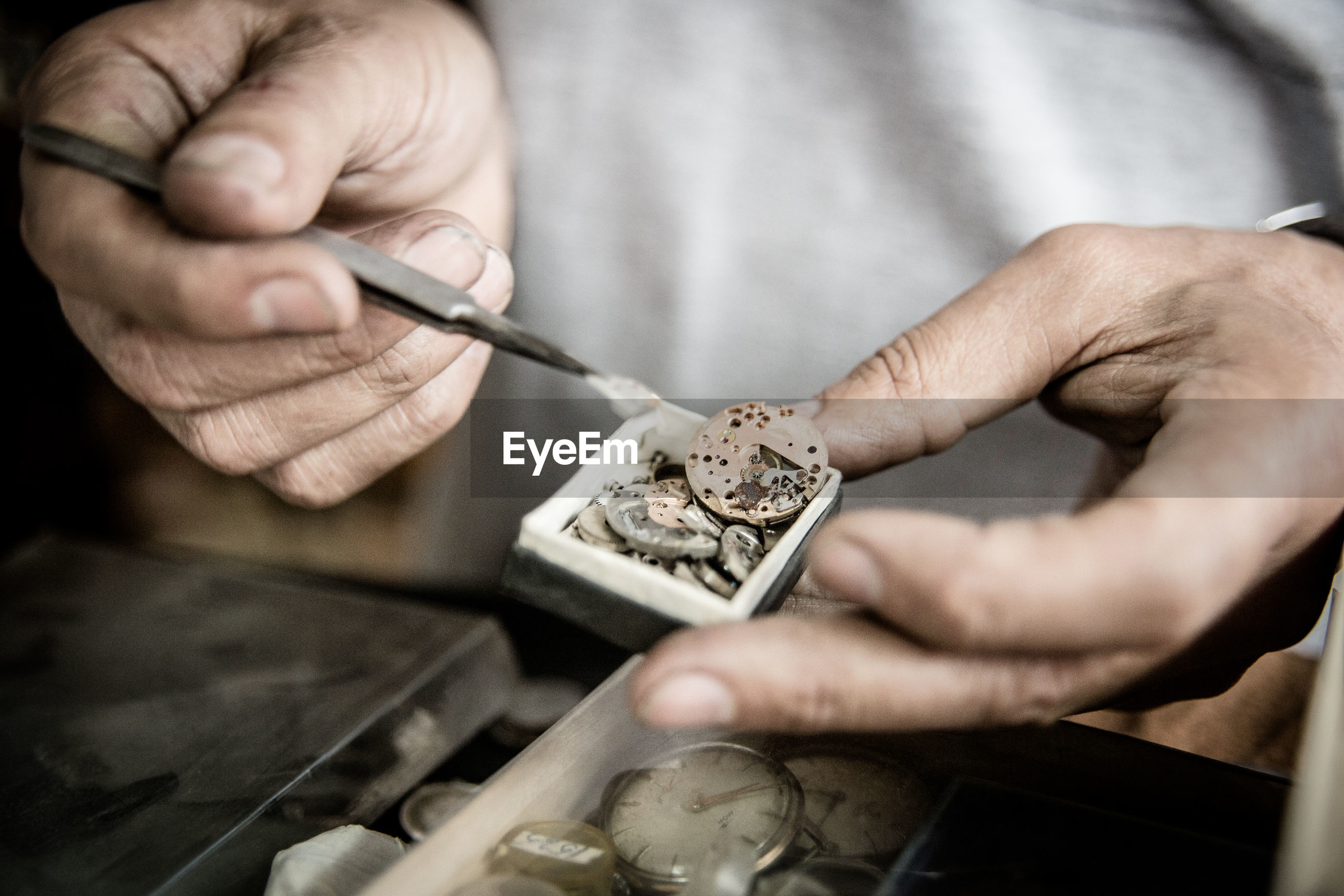 Close-up of hand repairing wristwatch