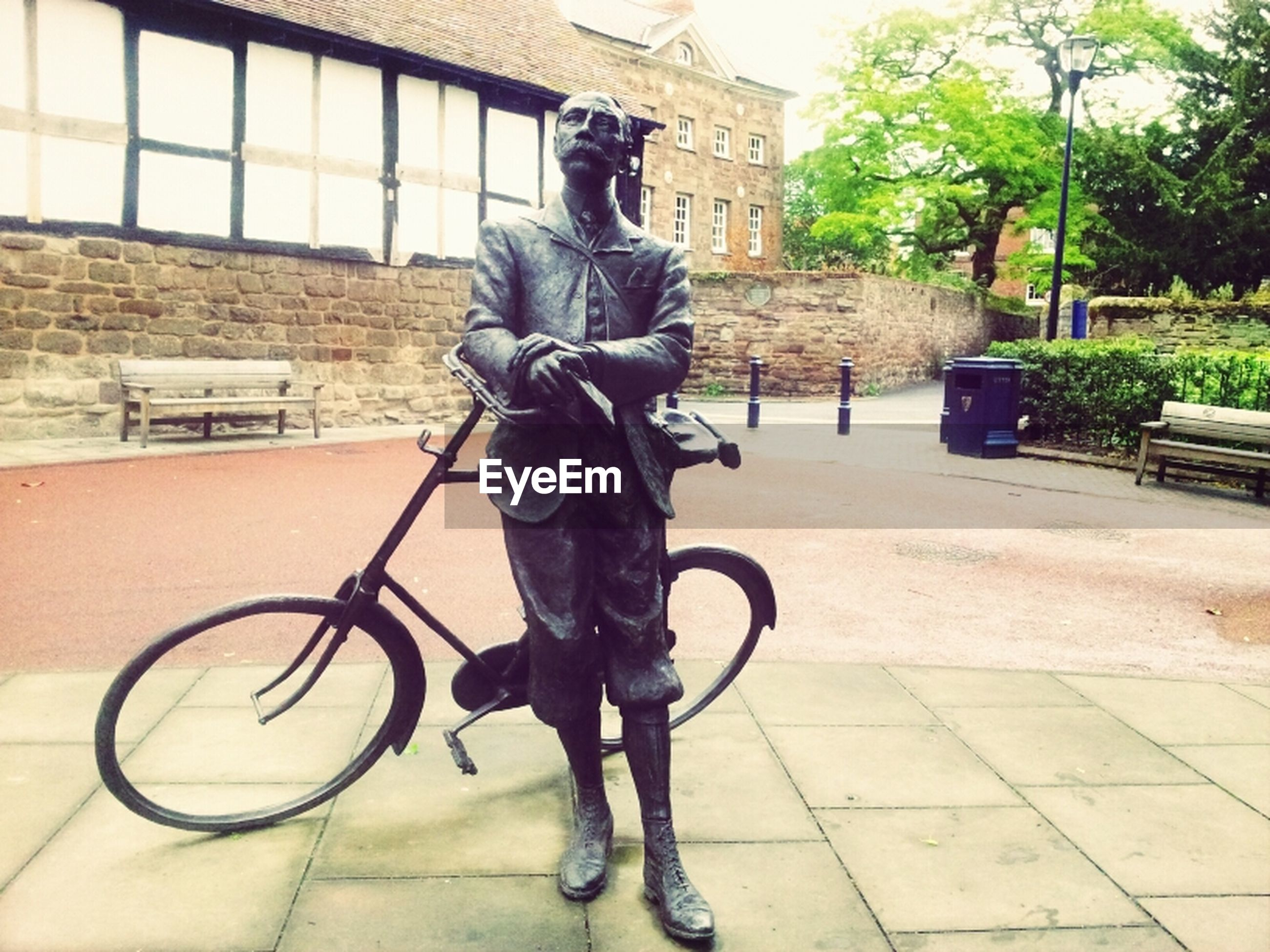 bicycle, building exterior, architecture, built structure, transportation, art and craft, art, mode of transport, street, land vehicle, sculpture, human representation, sidewalk, statue, creativity, city, full length, parking, day, outdoors