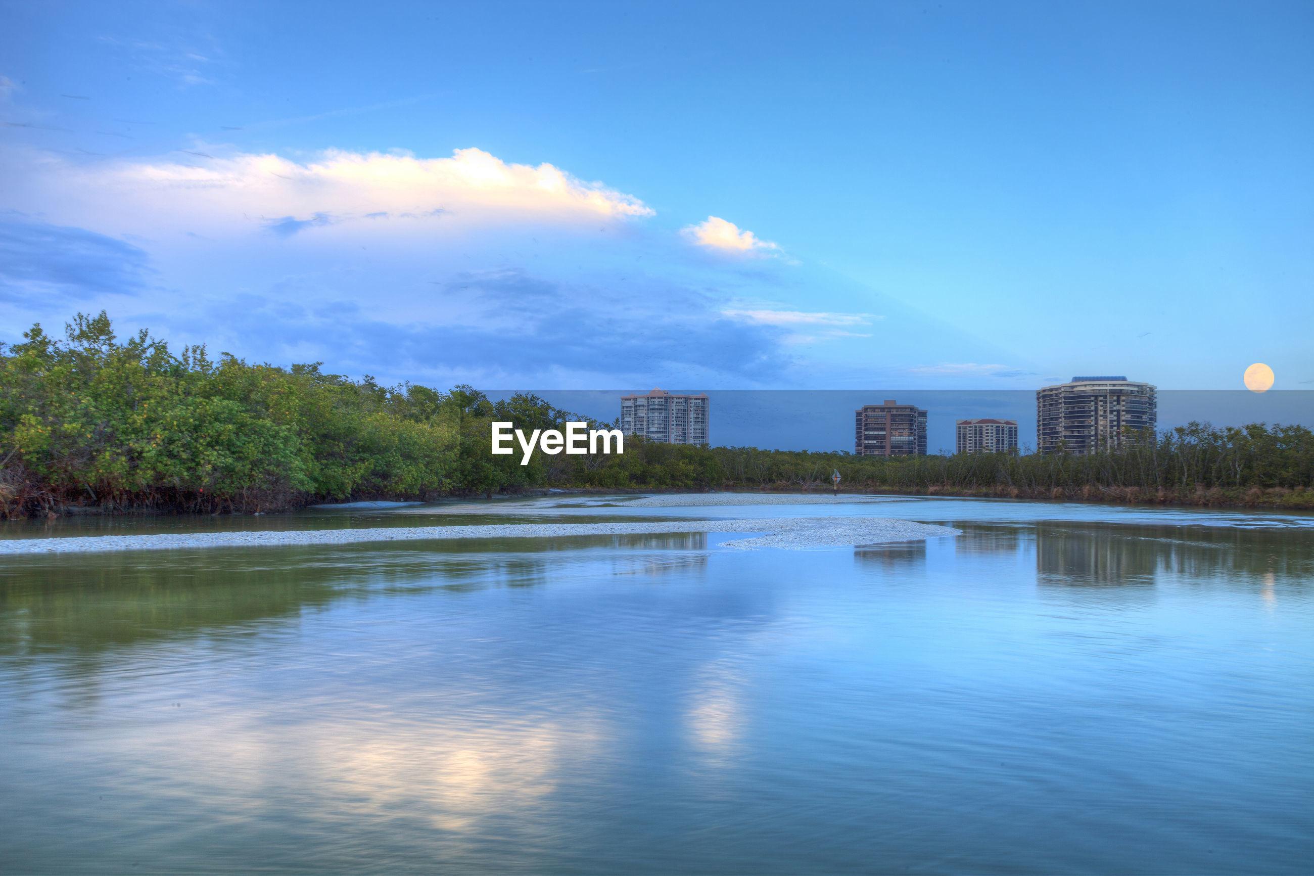 LAKE BY BUILDINGS AGAINST BLUE SKY