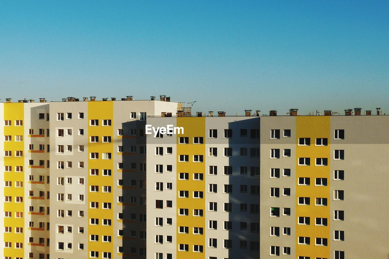 Low angle view of residential buildings against clear blue sky