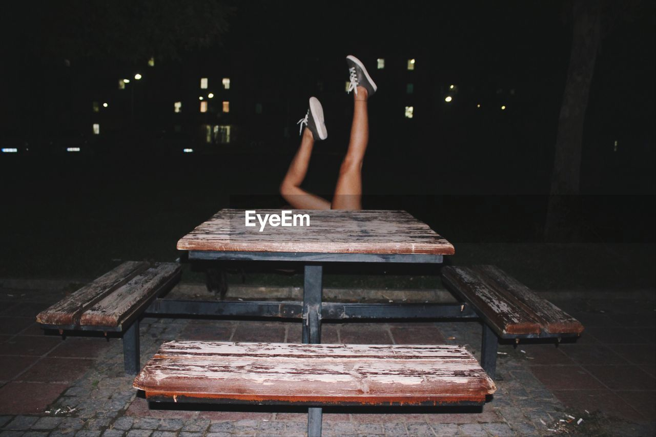 Woman Lying With Feet Up By Bench At Night