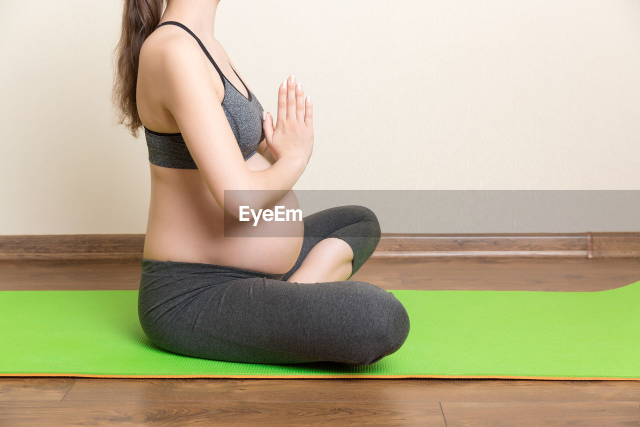 MIDSECTION OF WOMAN SITTING ON WALL