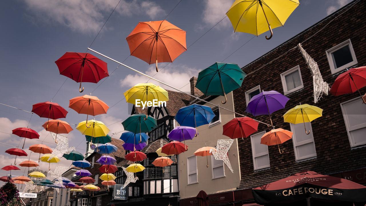 multi colored, umbrella, built structure, architecture, hanging, protection, low angle view, sky, building exterior, decoration, no people, city, security, nature, outdoors, day, building, parasol, variation