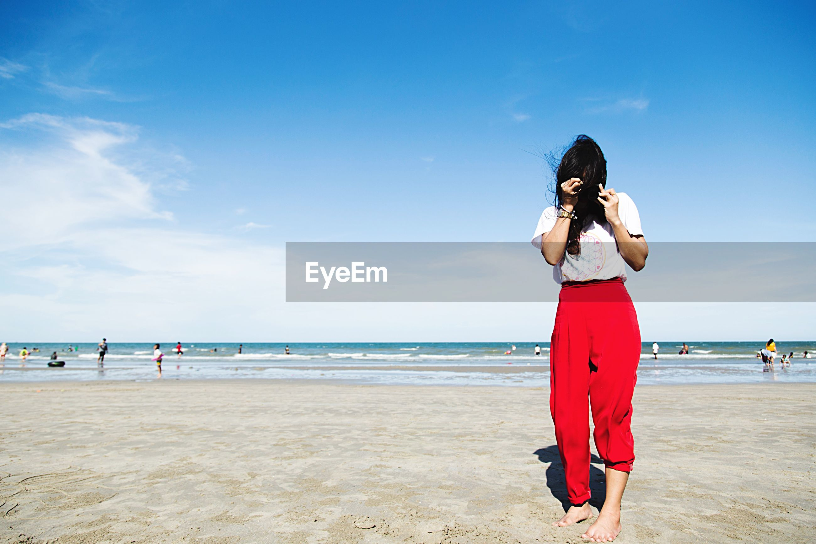 Woman with hair covering face standing at beach against sky