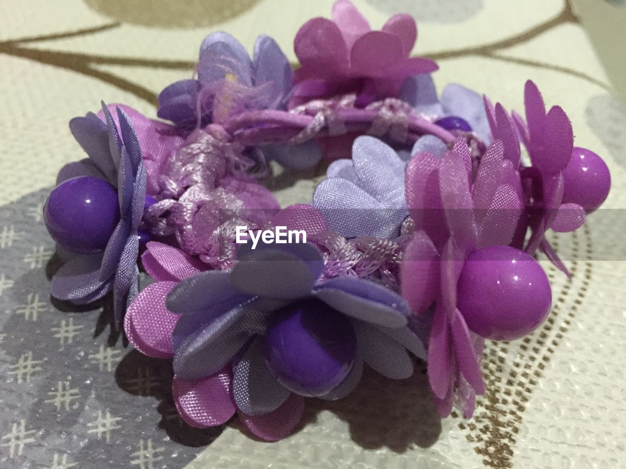 flower, petal, purple, indoors, gift, no people, flower head, celebration, beauty in nature, close-up, fragility, pink color, high angle view, nature, ribbon - sewing item, ribbon, day, freshness