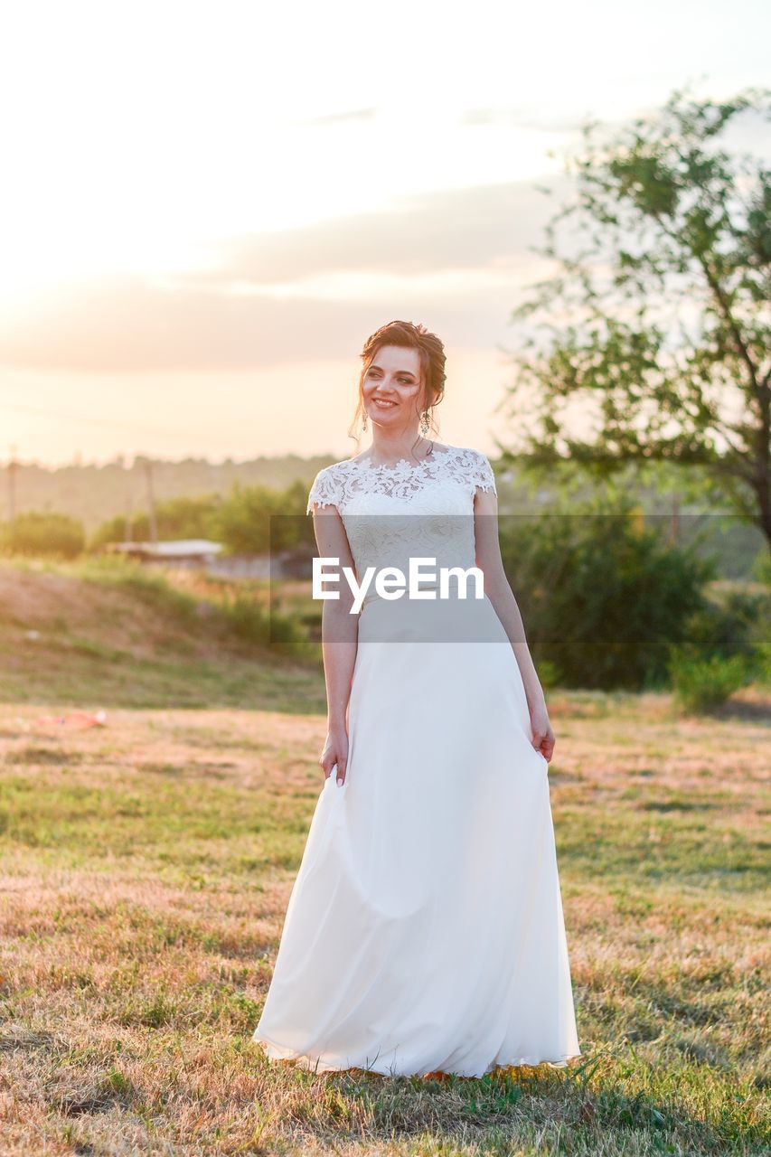 Woman wearing wedding dress while standing on field against sky during sunset