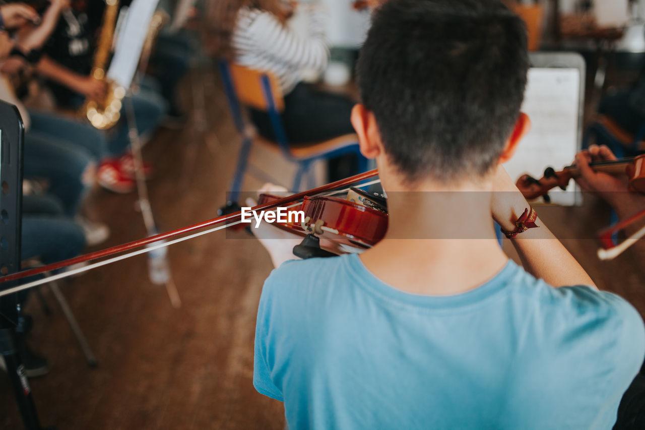 Rear View Of Men Playing Violin
