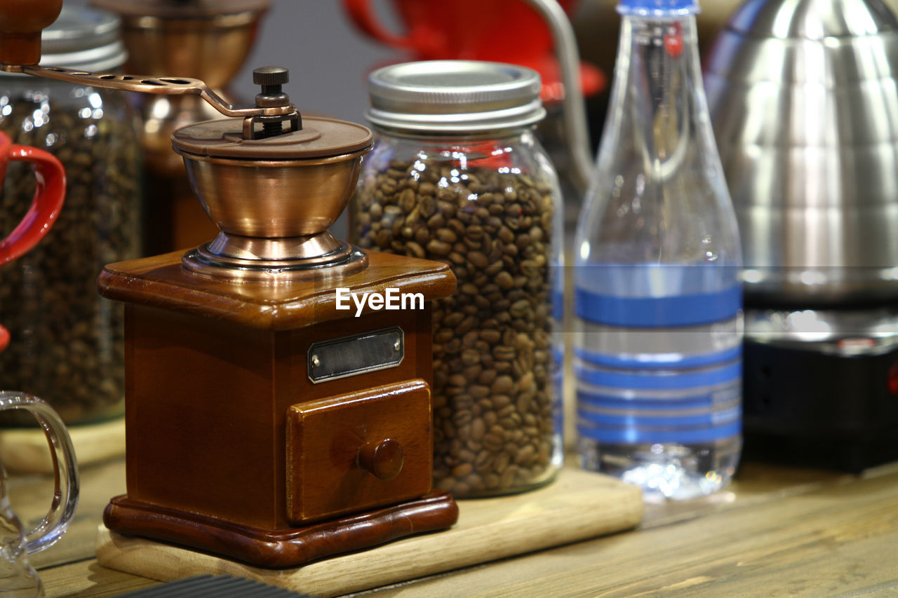 container, table, wood - material, indoors, still life, food and drink, close-up, no people, focus on foreground, technology, retro styled, selective focus, antique, metal, cafe, coffee, jar, coffee - drink, appliance