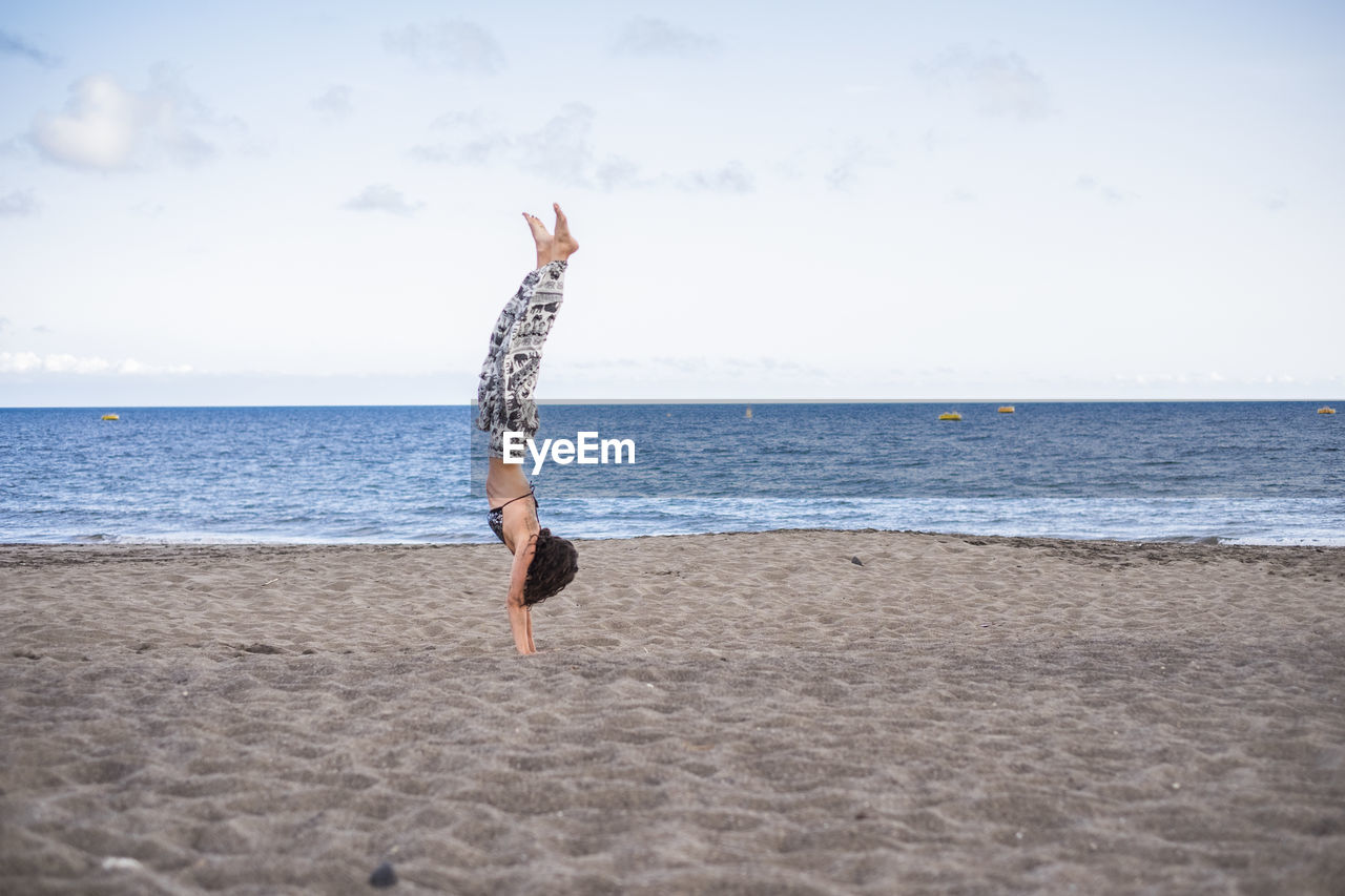Side View Of Woman Practicing Handstand At Beach