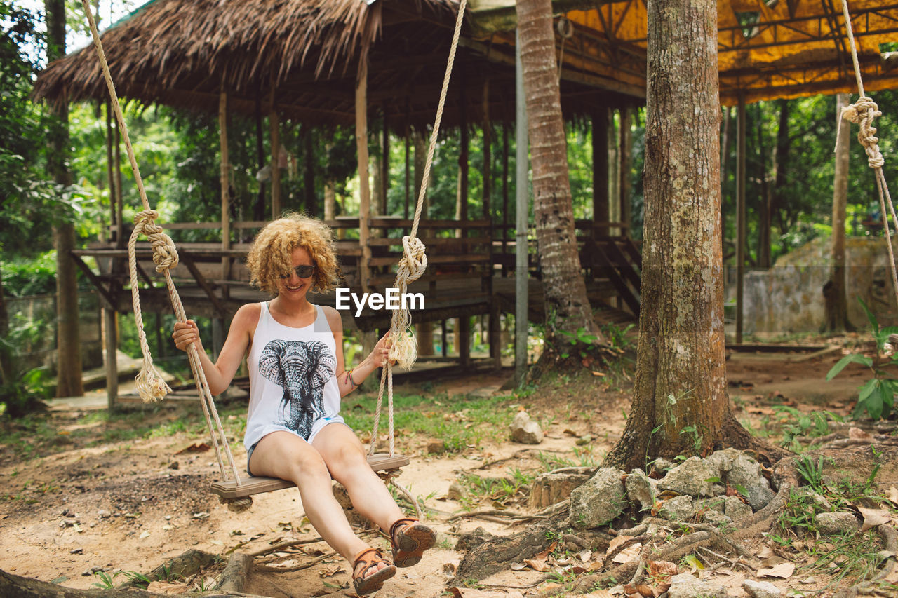 Full Length Of Woman Sitting On Swing In Forest