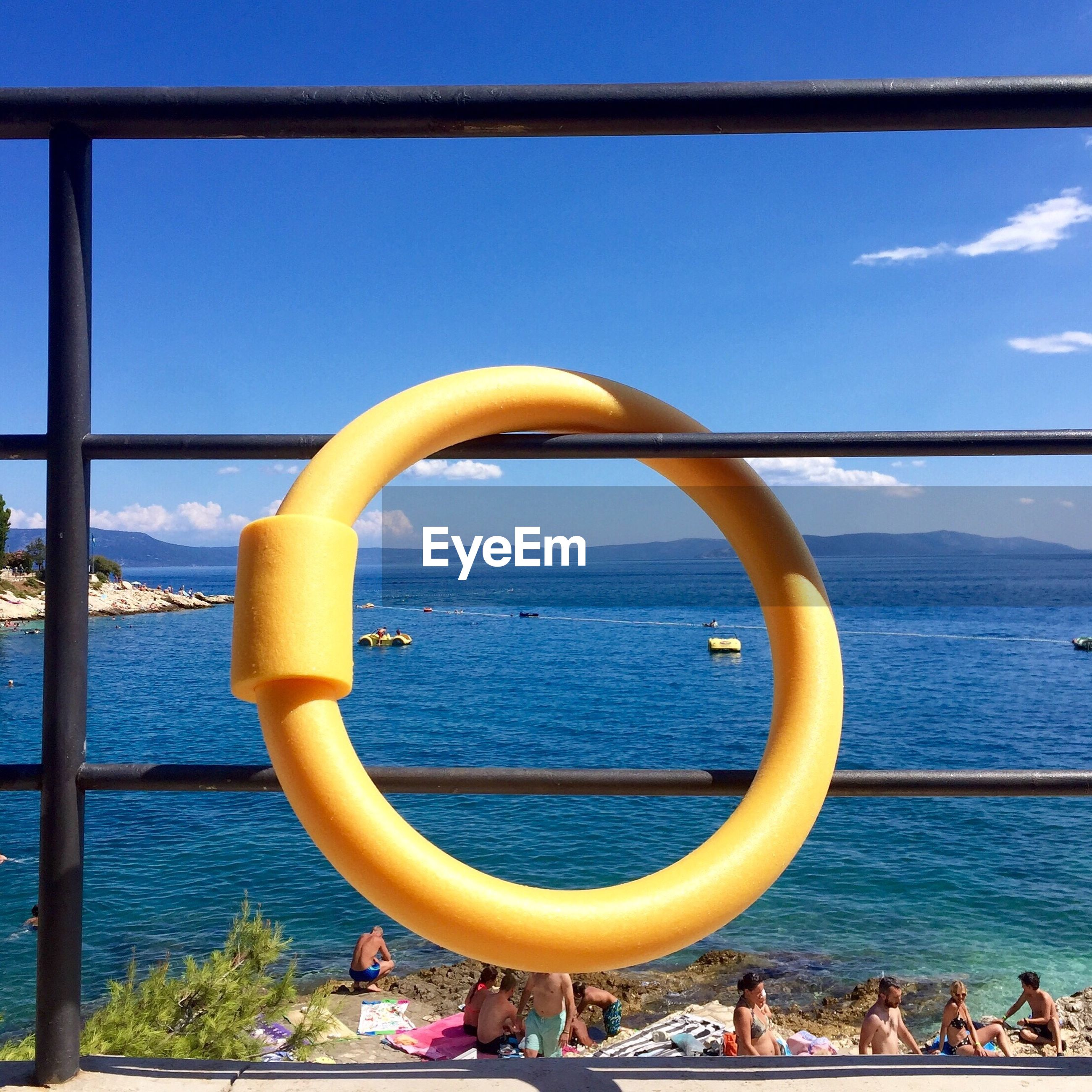Inflatable ring hanging on railing against sea