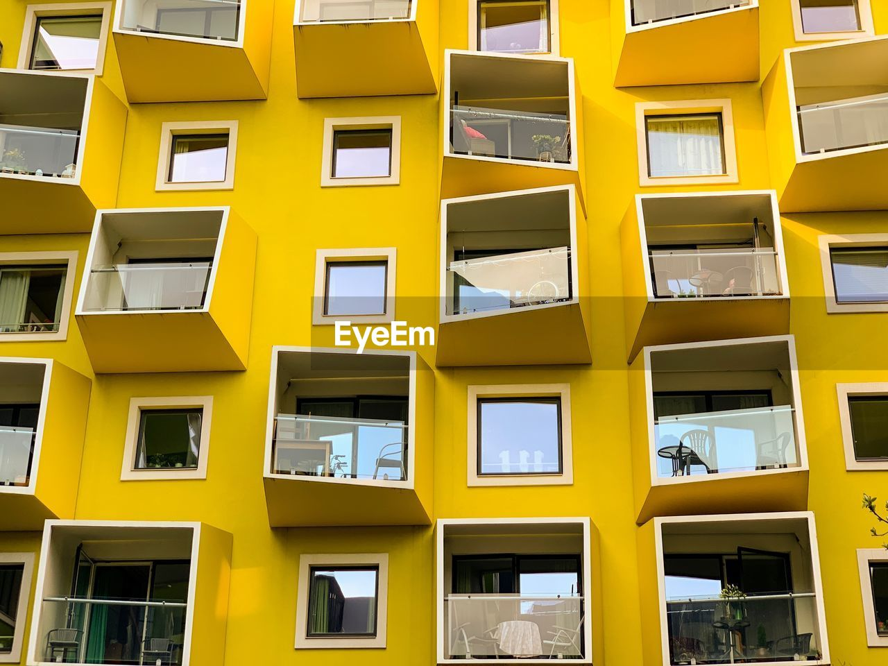yellow, architecture, built structure, building exterior, window, residential district, building, backgrounds, no people, full frame, city, repetition, low angle view, day, apartment, balcony, glass - material, in a row, outdoors, pattern