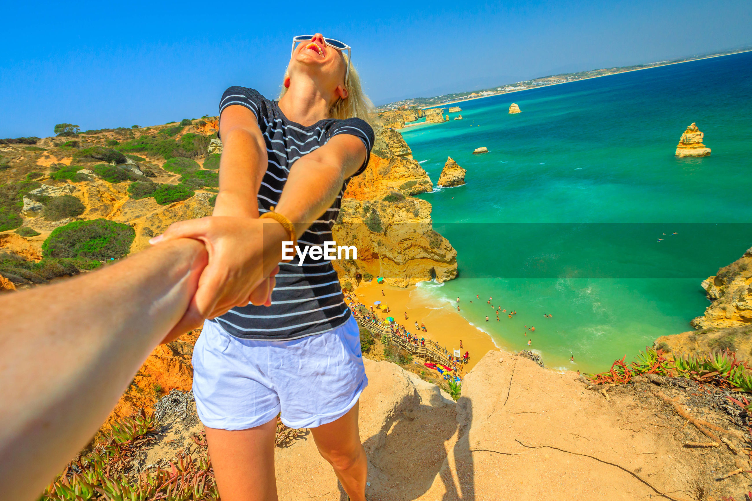 Happy woman holding cropped hand against sea