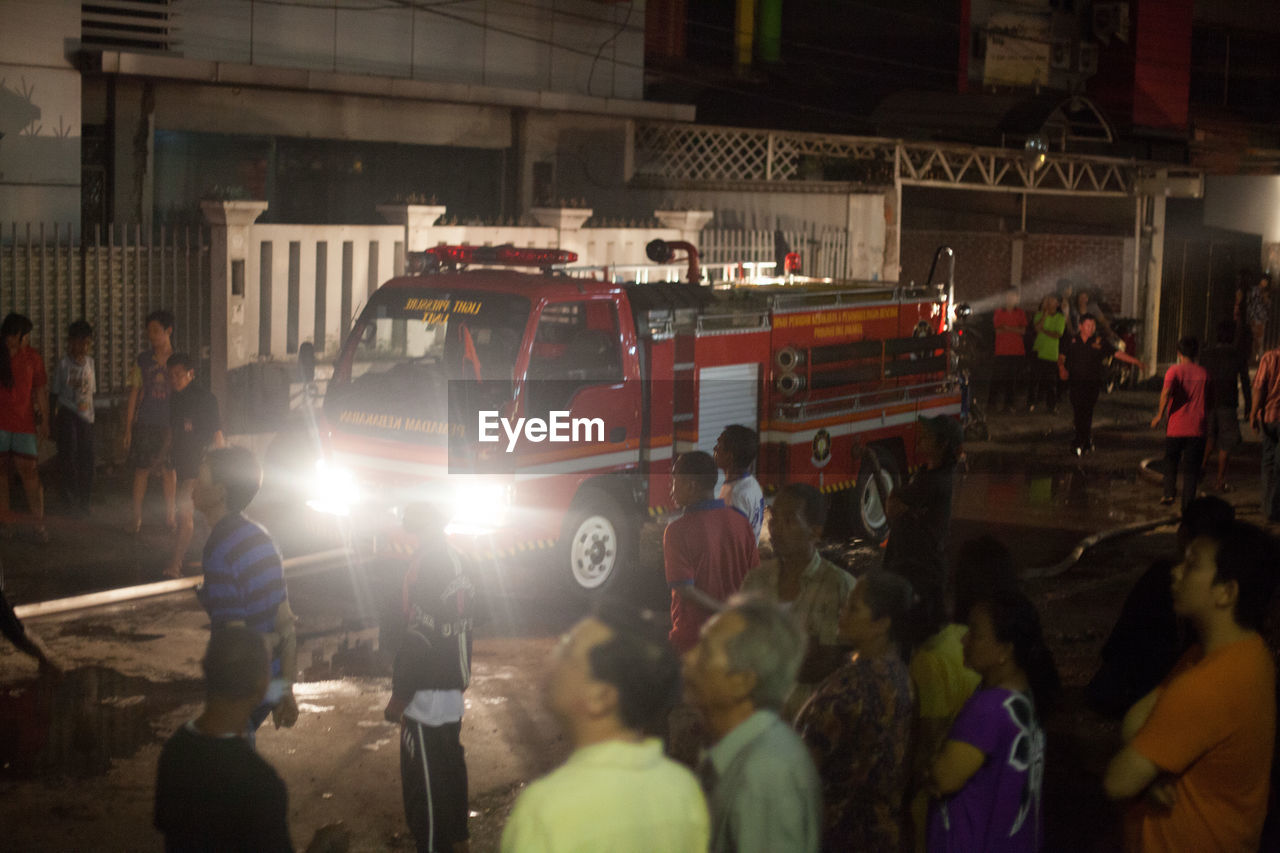 accidents and disasters, real people, land vehicle, building exterior, fire engine, men, transportation, night, occupation, large group of people, architecture, built structure, working, firefighter, outdoors, illuminated, crowd, riot, adult, people