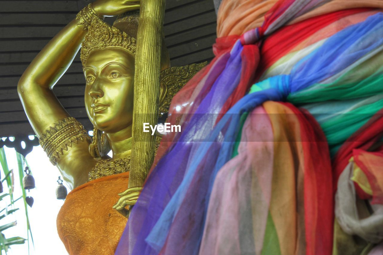 Gold colored statue by colorful scarfs in temple