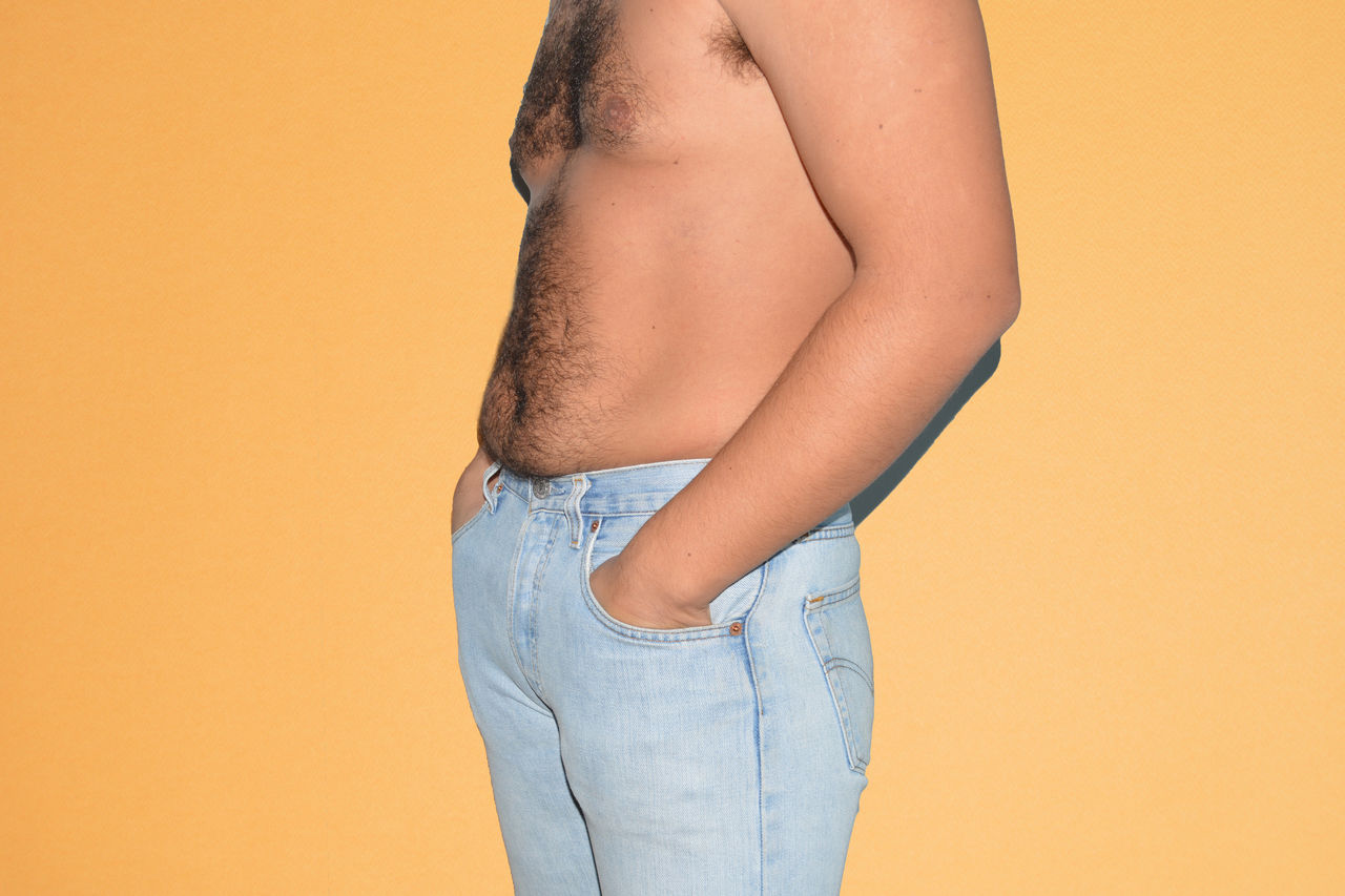 Midsection of man with hands in pockets over beige background
