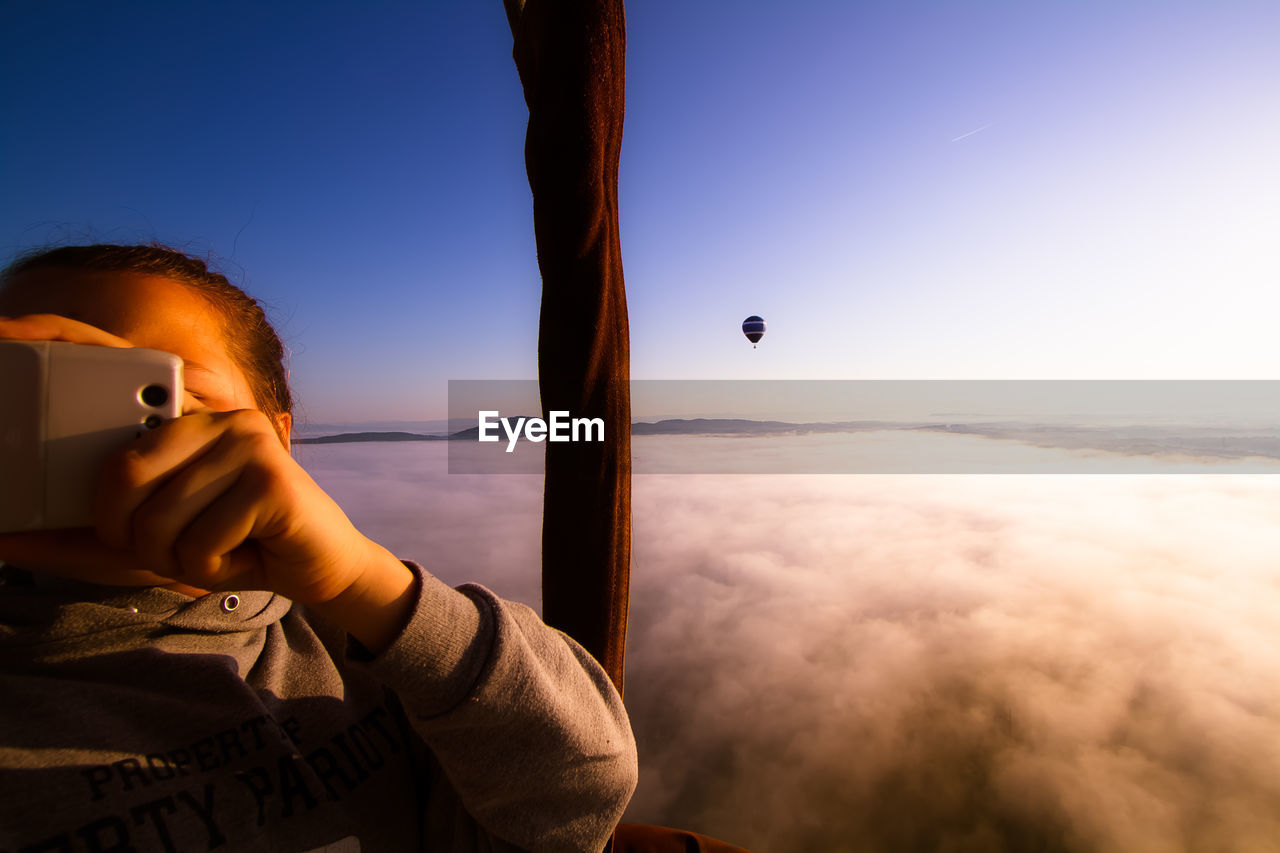 Man Photographing Cloudscape With Cell Phone, Balloon In Distance