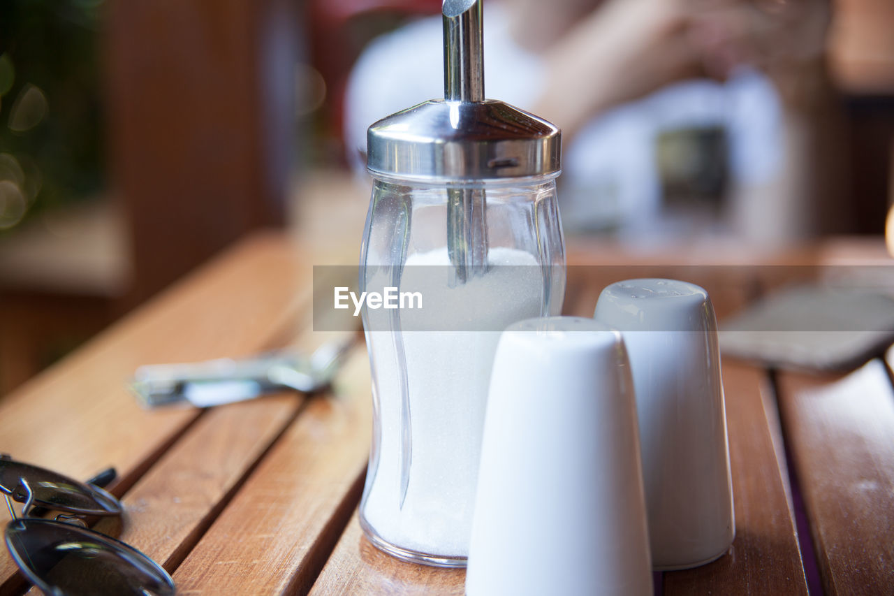 Close-up of salt shaker with empty drinking glasses by sunglasses on table