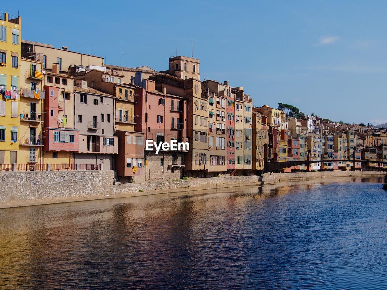 River Flowing By Buildings Against Sky