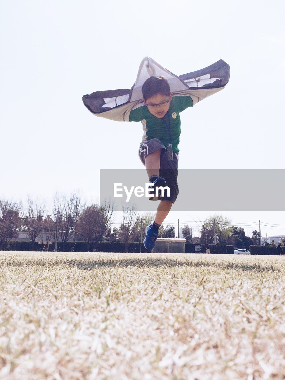 full length, one person, mid-air, motion, jumping, day, leisure activity, outdoors, real people, lifestyles, casual clothing, field, clear sky, fun, childhood, boys, tree, happiness, sky, grass, nature, energetic, people