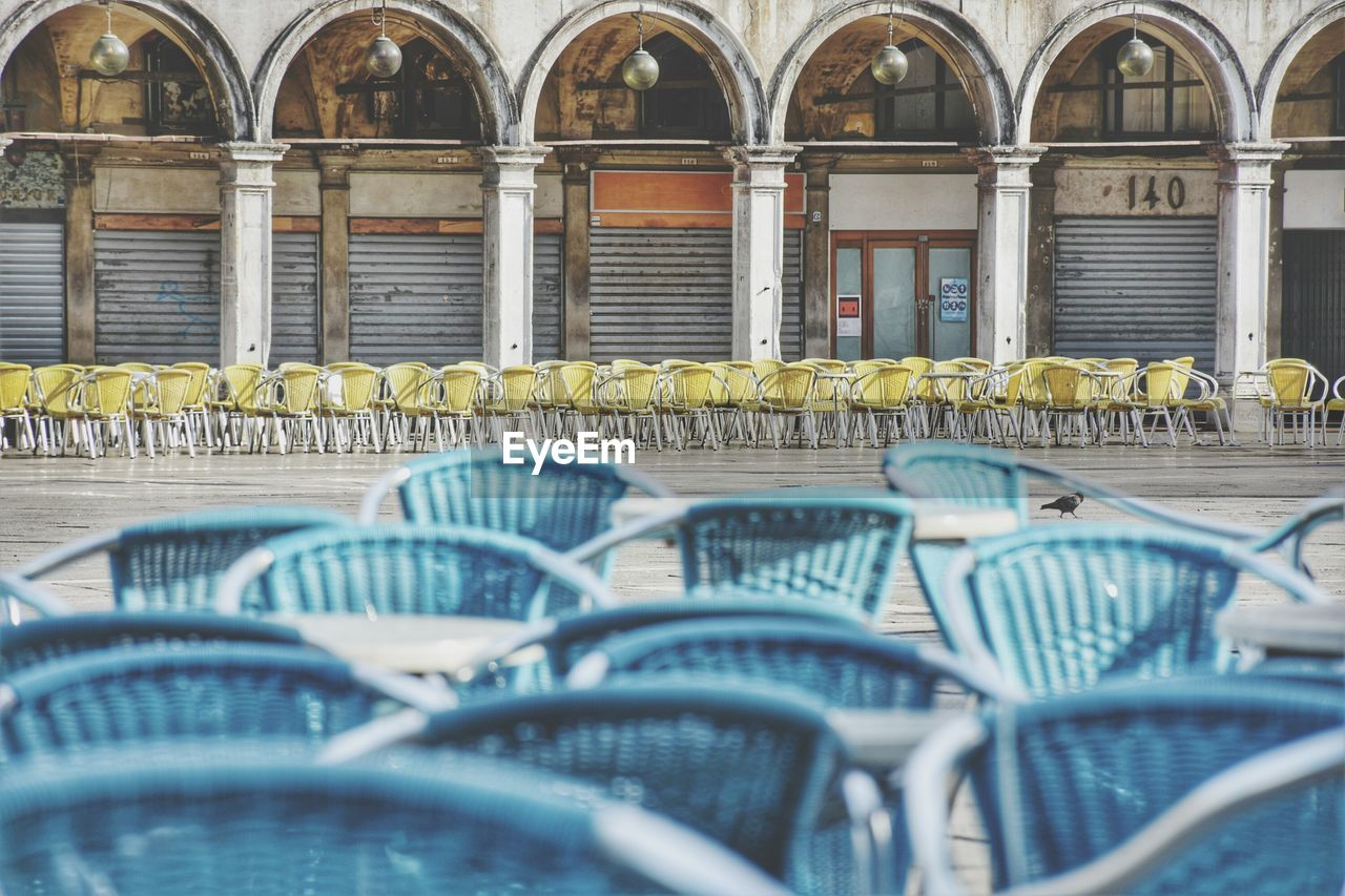 chair, architecture, seat, in a row, built structure, no people, day, side by side, large group of objects, selective focus, arch, arrangement, repetition, building exterior, order, yellow, empty, metal, outdoors, absence, surface level, consumerism