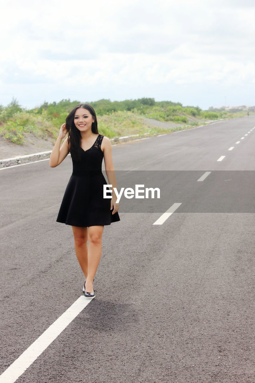road, full length, road marking, real people, young adult, young women, lifestyles, one person, front view, high heels, outdoors, standing, leisure activity, beautiful woman, looking at camera, portrait, day, sky, nature