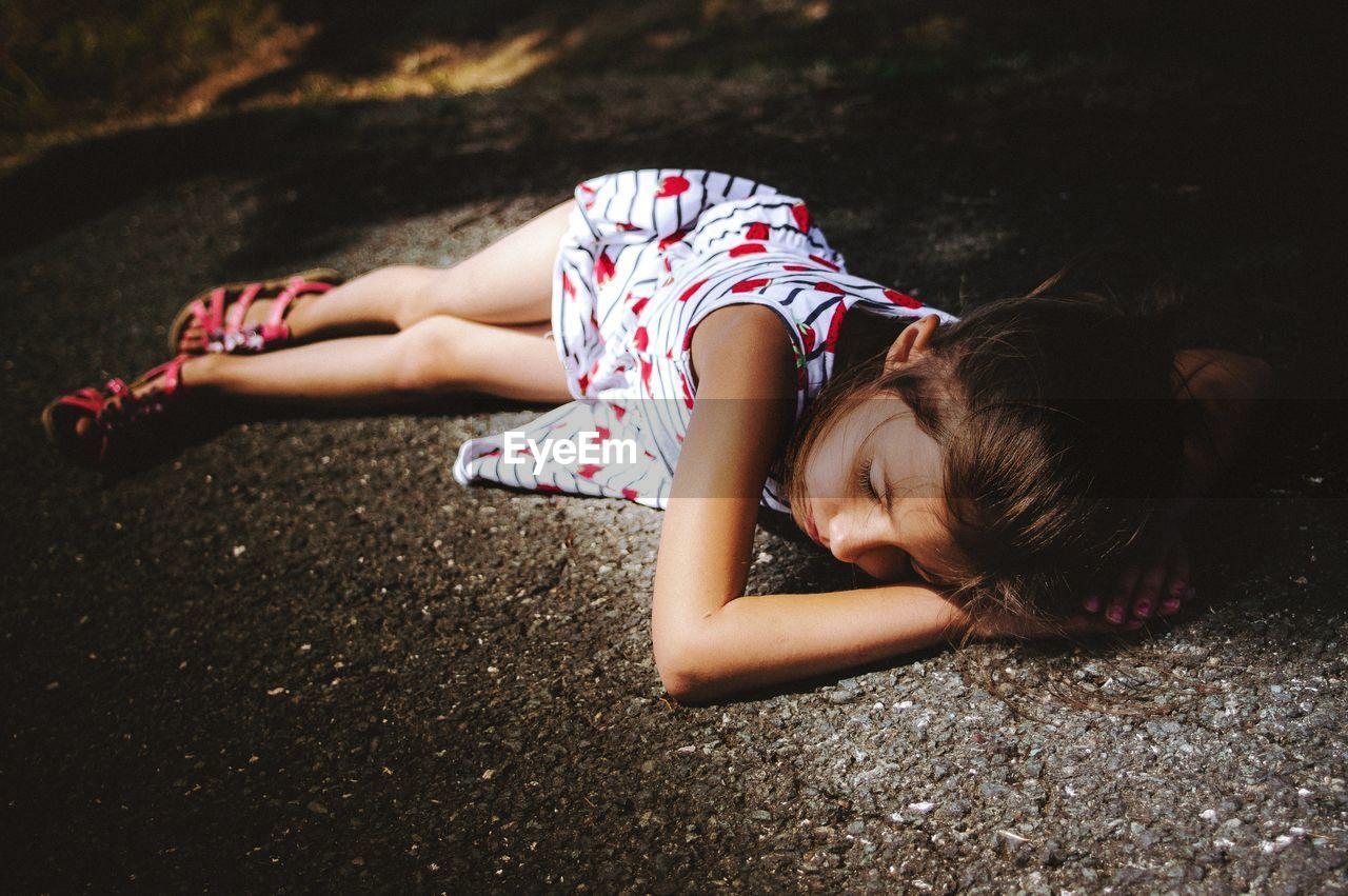 Full Length Of Girl Lying On Road