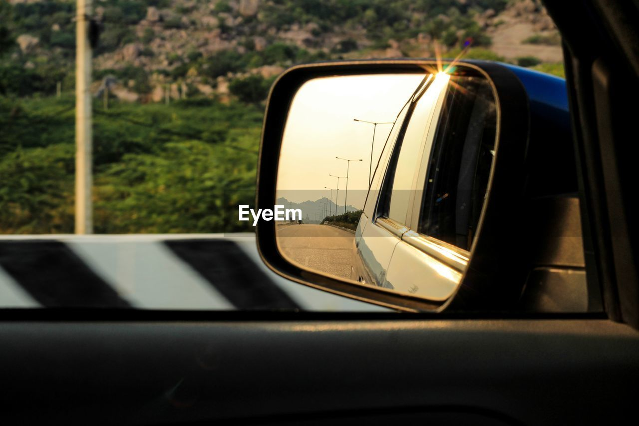 mode of transportation, land vehicle, transportation, car, motor vehicle, reflection, side-view mirror, glass - material, no people, travel, close-up, outdoors, day, window, mirror, road, tree, vehicle interior, nature, focus on foreground, vehicle mirror
