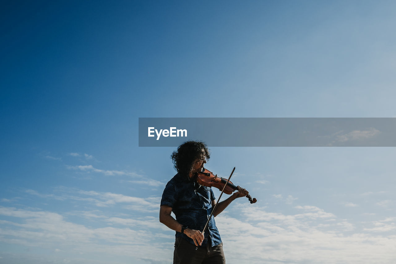 Low angle view of man playing violin against blue sky